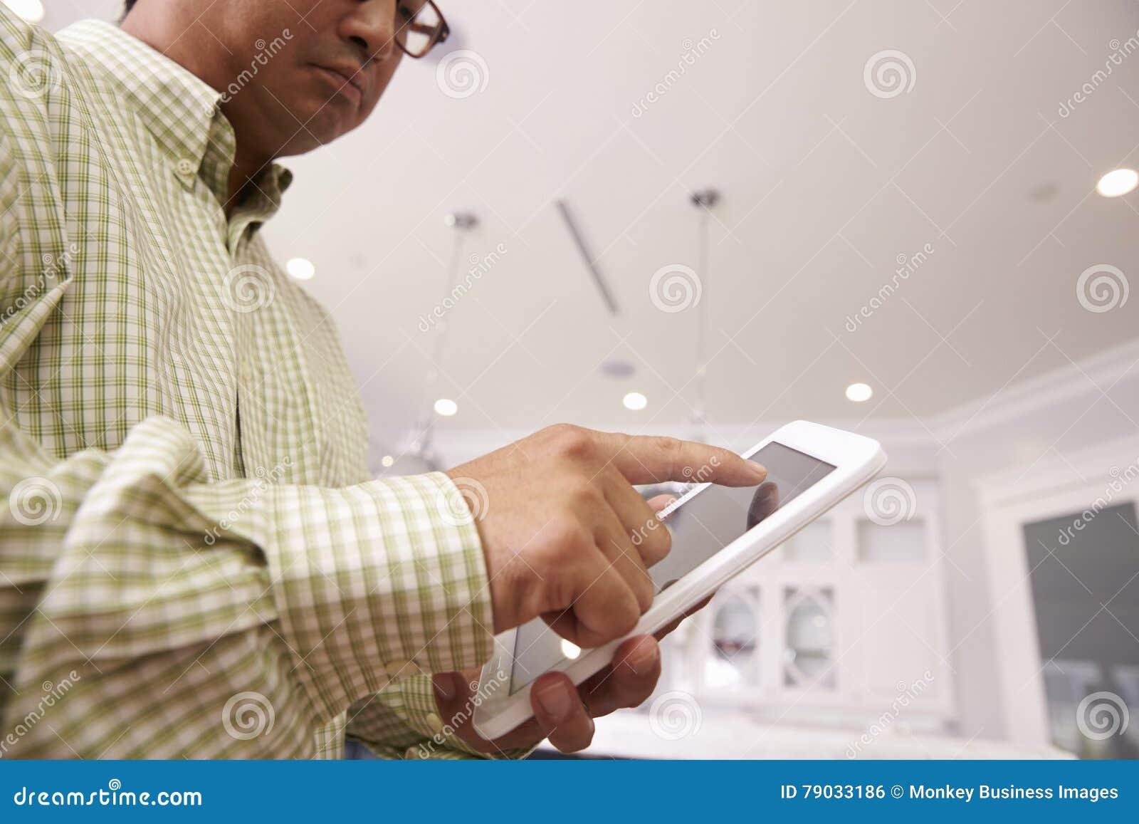 Man som använder den Digital minnestavlan för att kontrollera att tända hemma