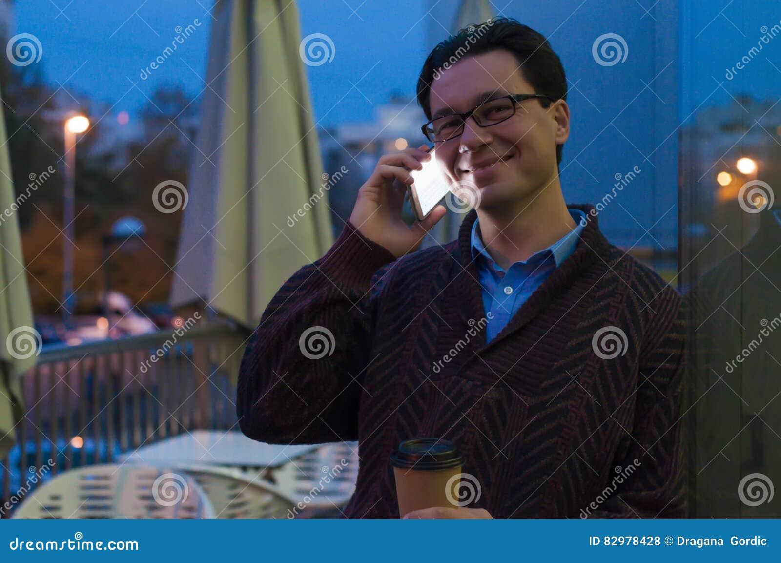Man som använder en telefon som smsar på smartphonen app och den pappers- koppen kaffe för innehav