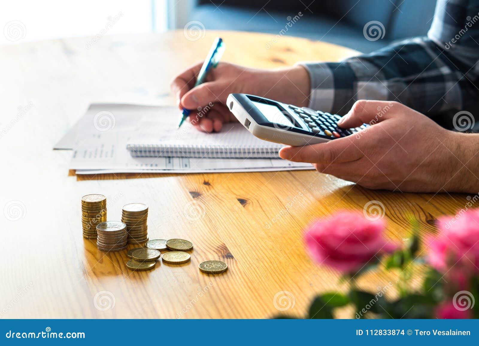 Man som använder räknemaskinen och räknar budgeten, kostnader och besparingar