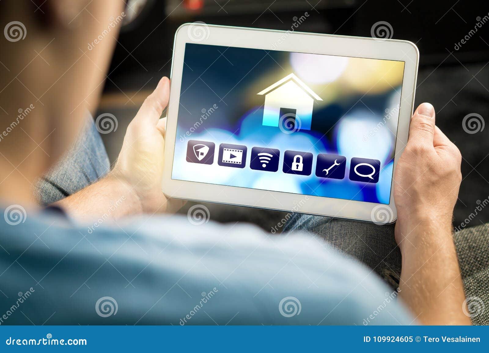 Man som använder smart hem- applikation i minnestavla för att kontrollera huset