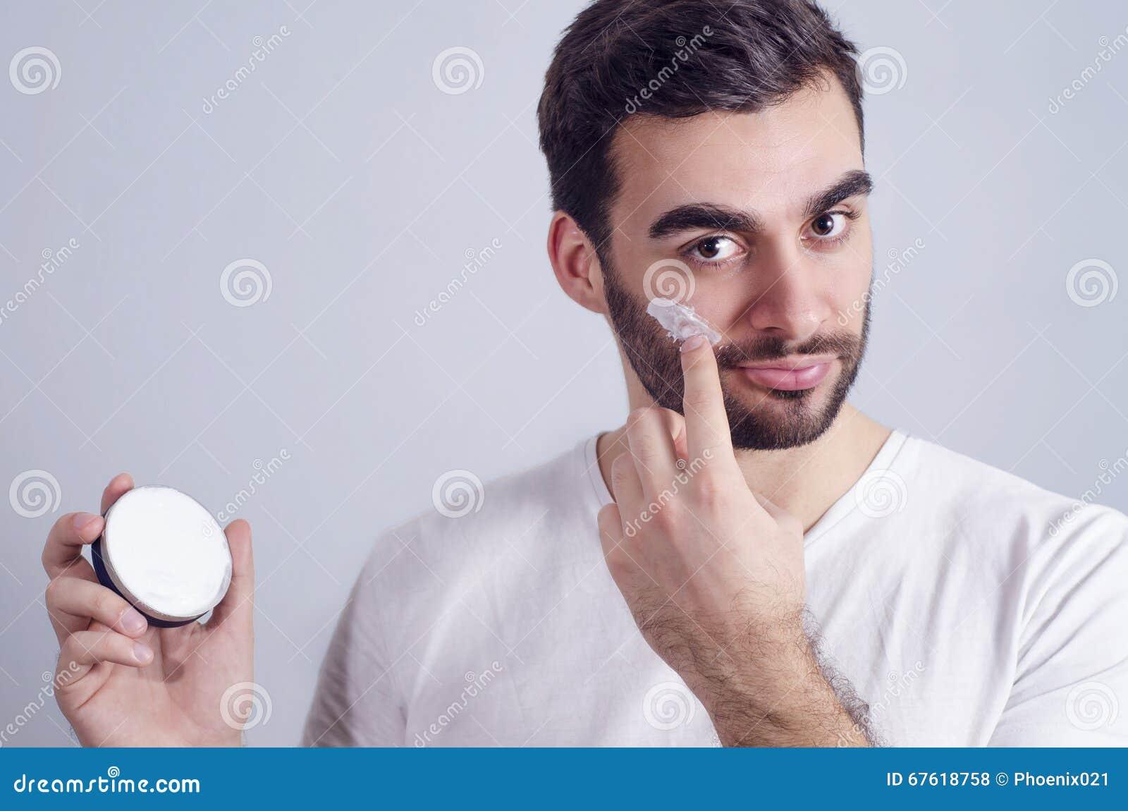 Man som applicerar framsidakräm på kinder