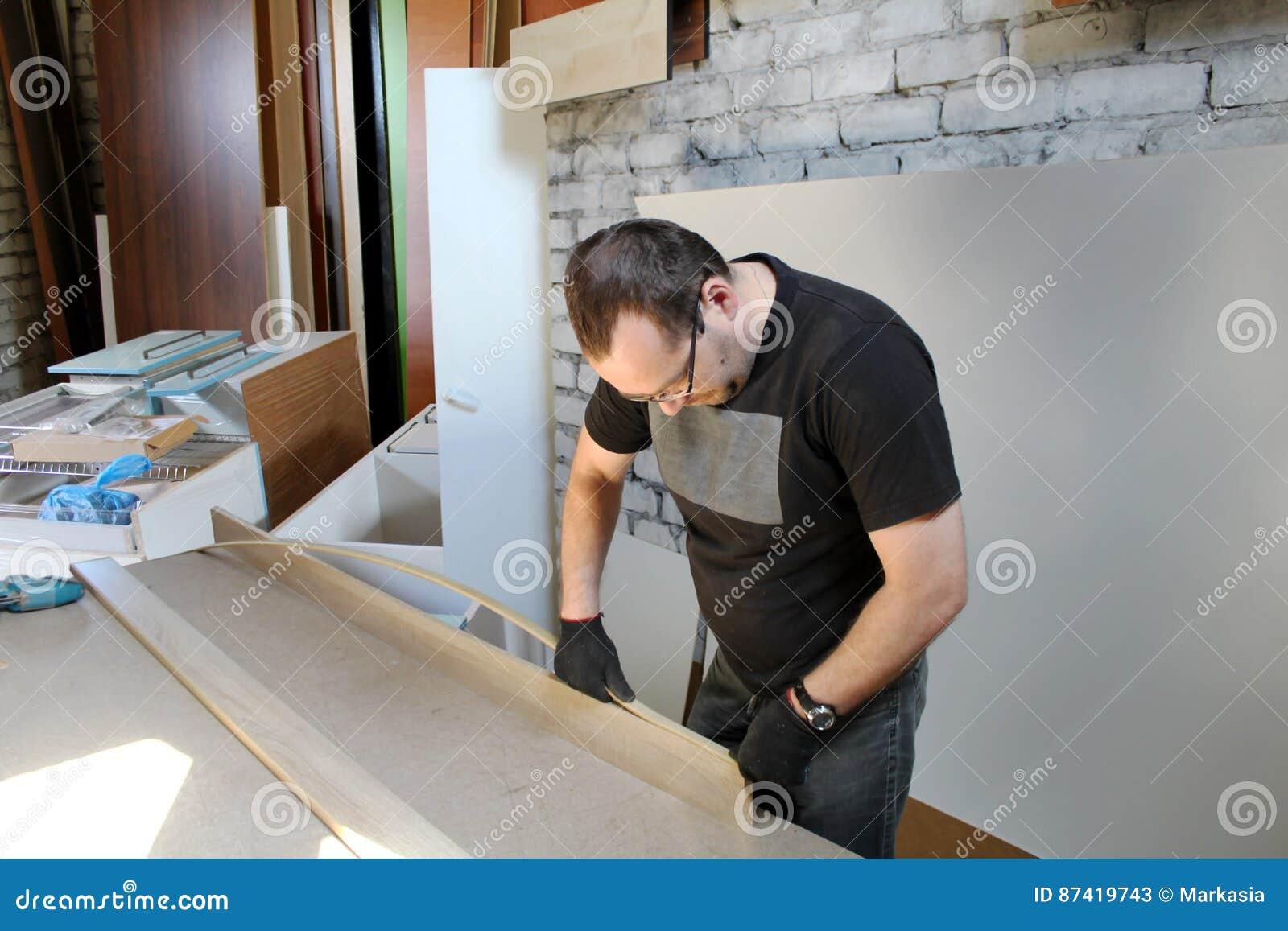 Man som arbetar med möblemang