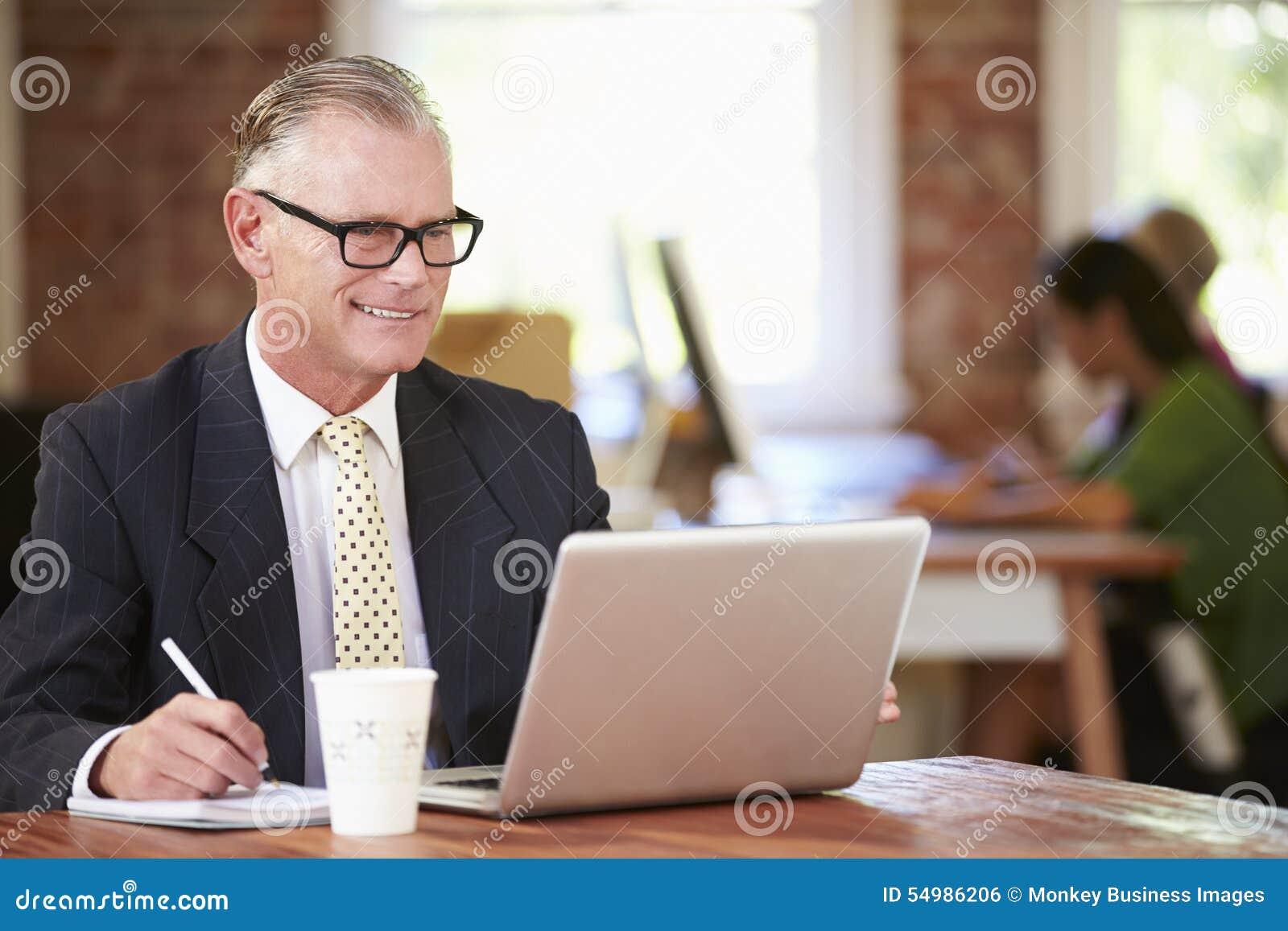 Man som arbetar på bärbara datorn i modernt kontor