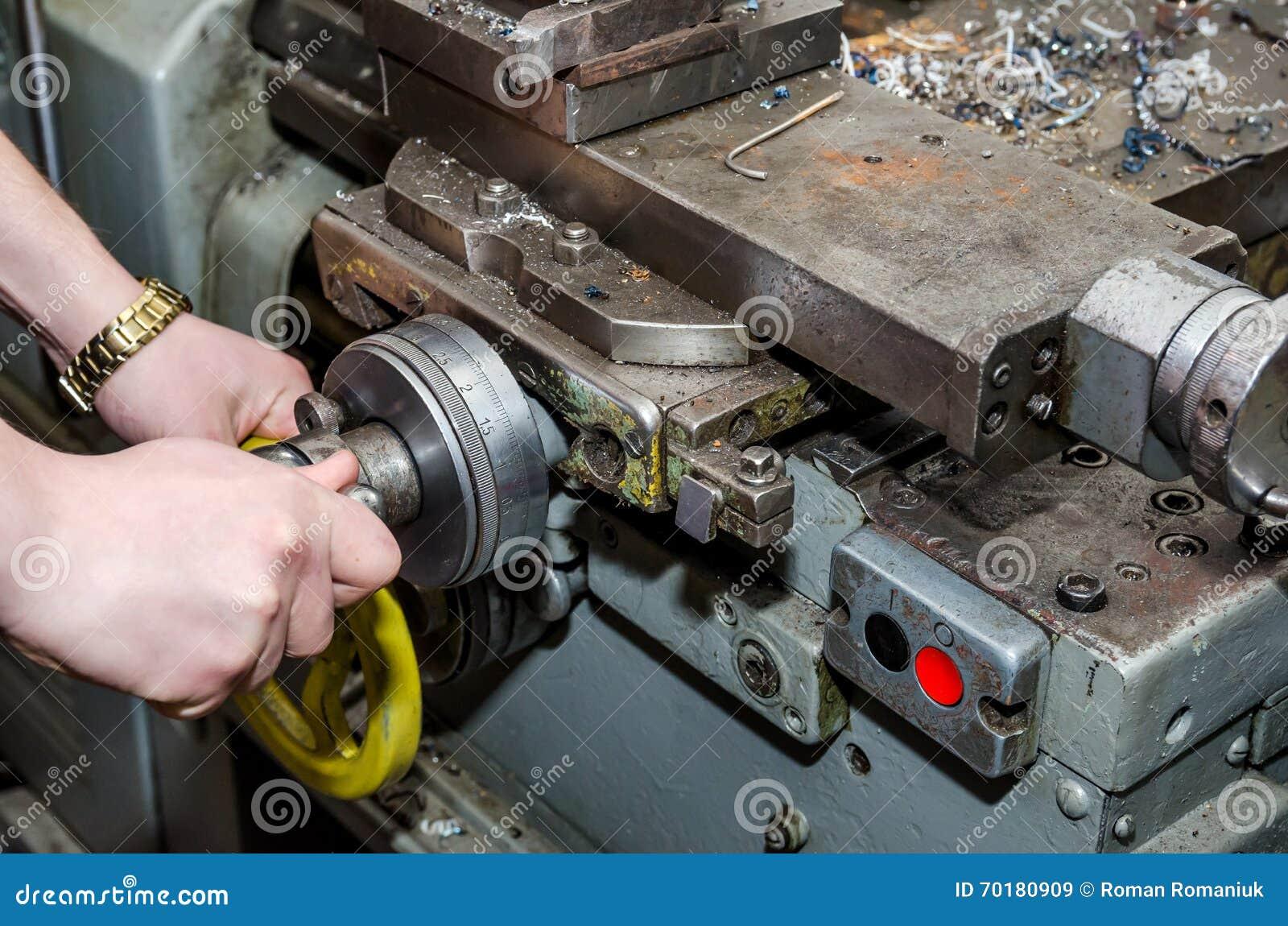 Man som arbetar på den industriella drejbänken