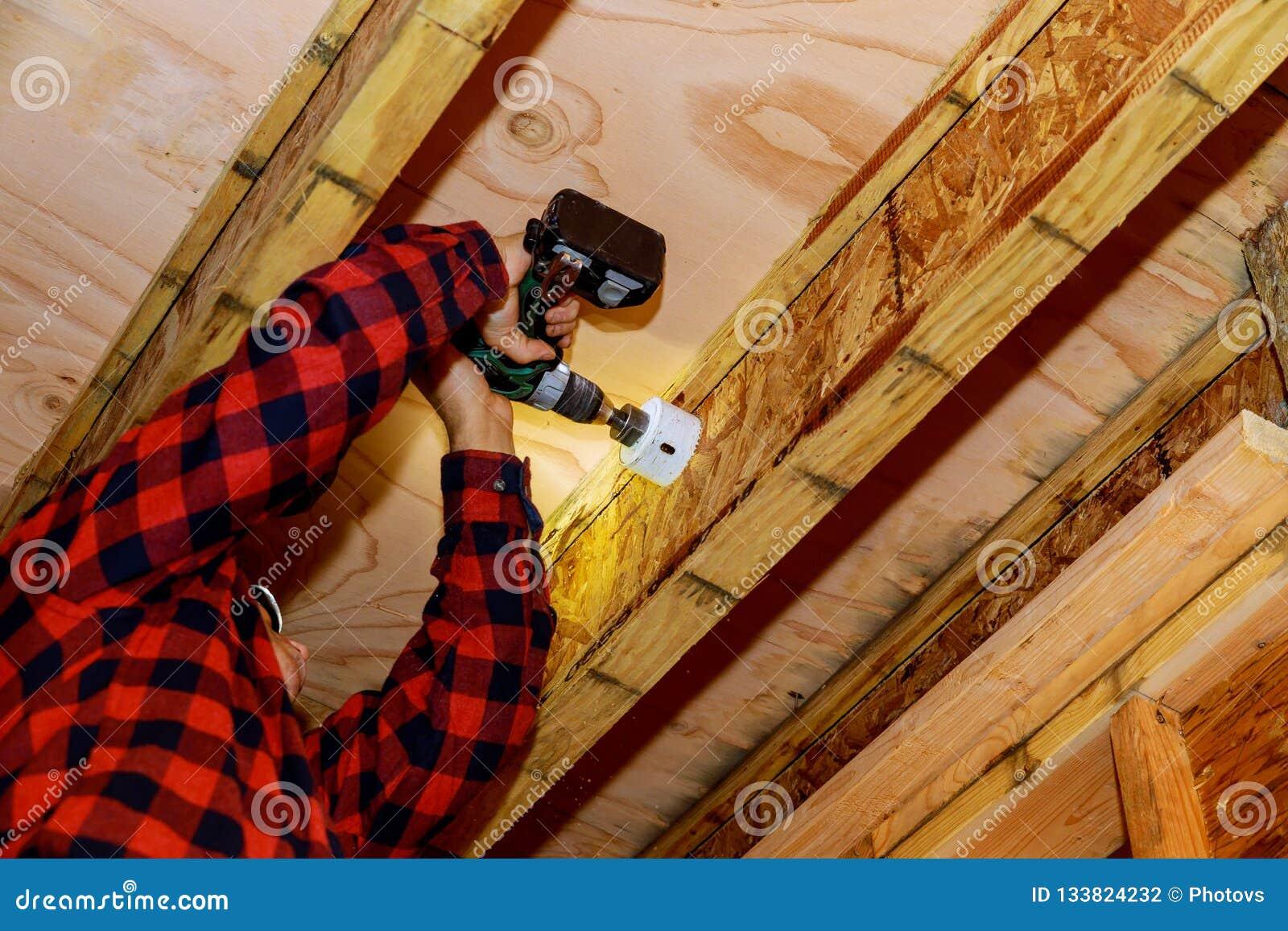 Man som bygger en träuteplats med att bulta skruva tillsammans strålar