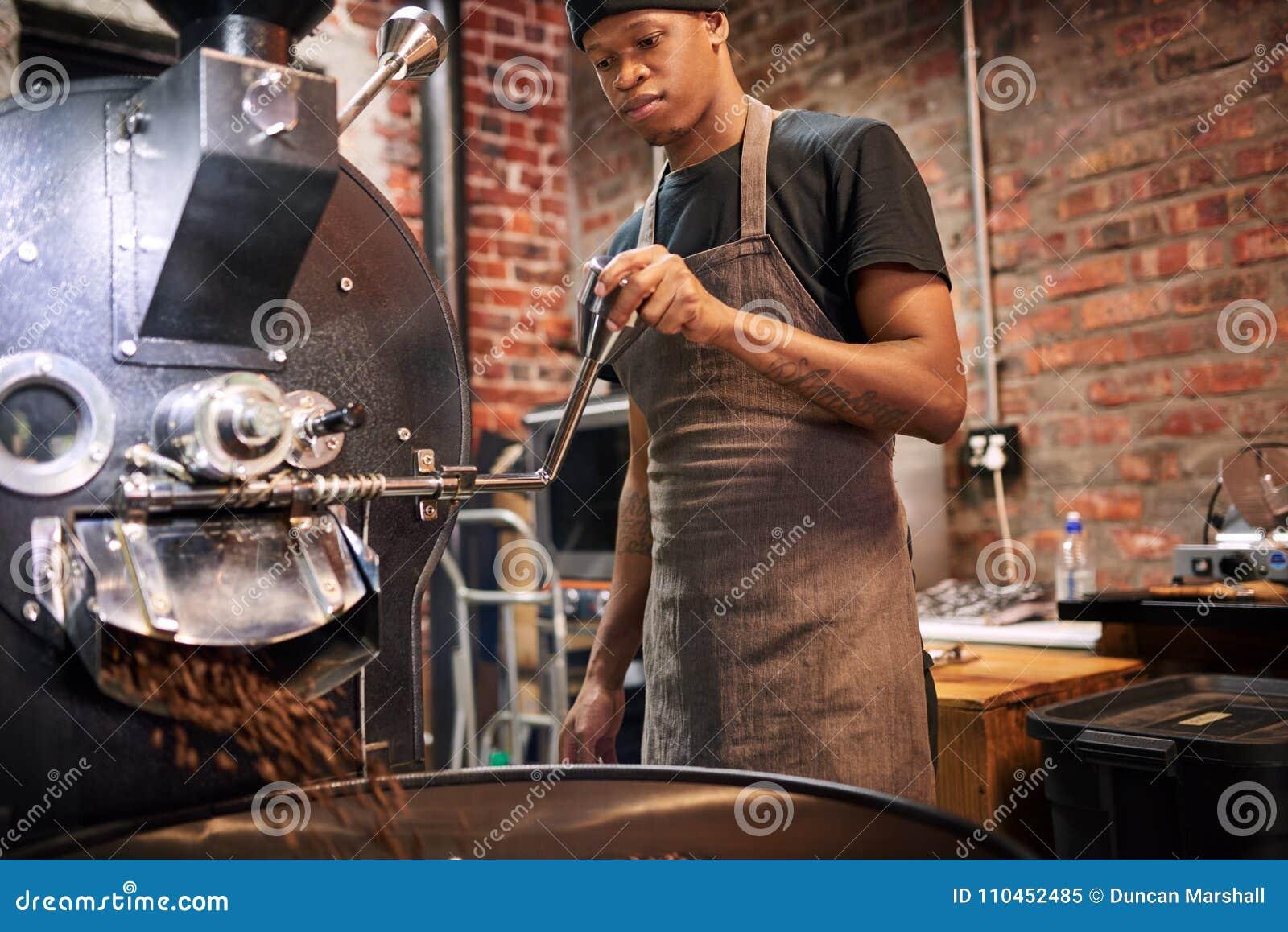Man som drar spaken för att hälla våra kaffebönor från kaffebrännaren