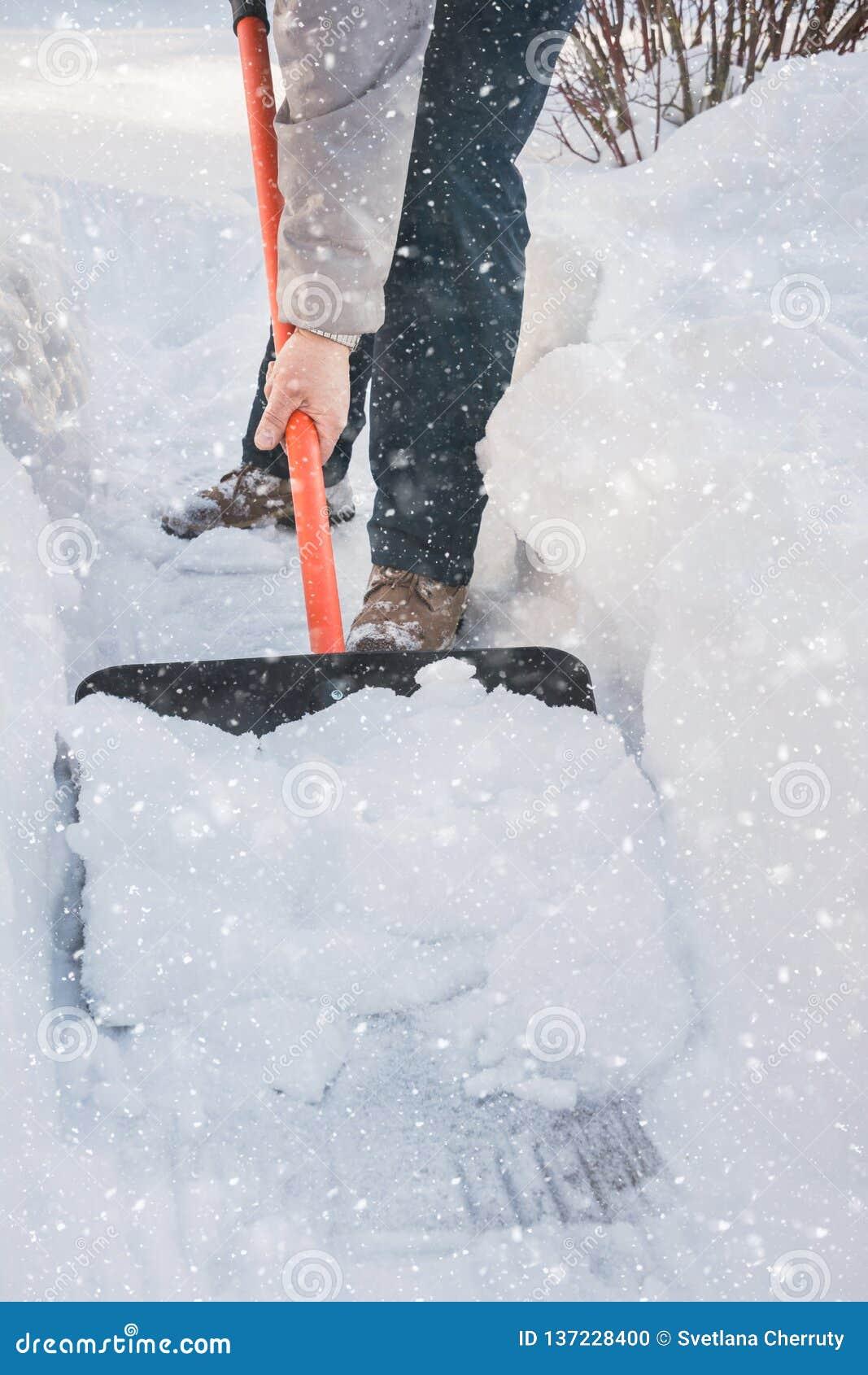 Man som gör klar snö förbi skyffeln efter snöfall utomhus