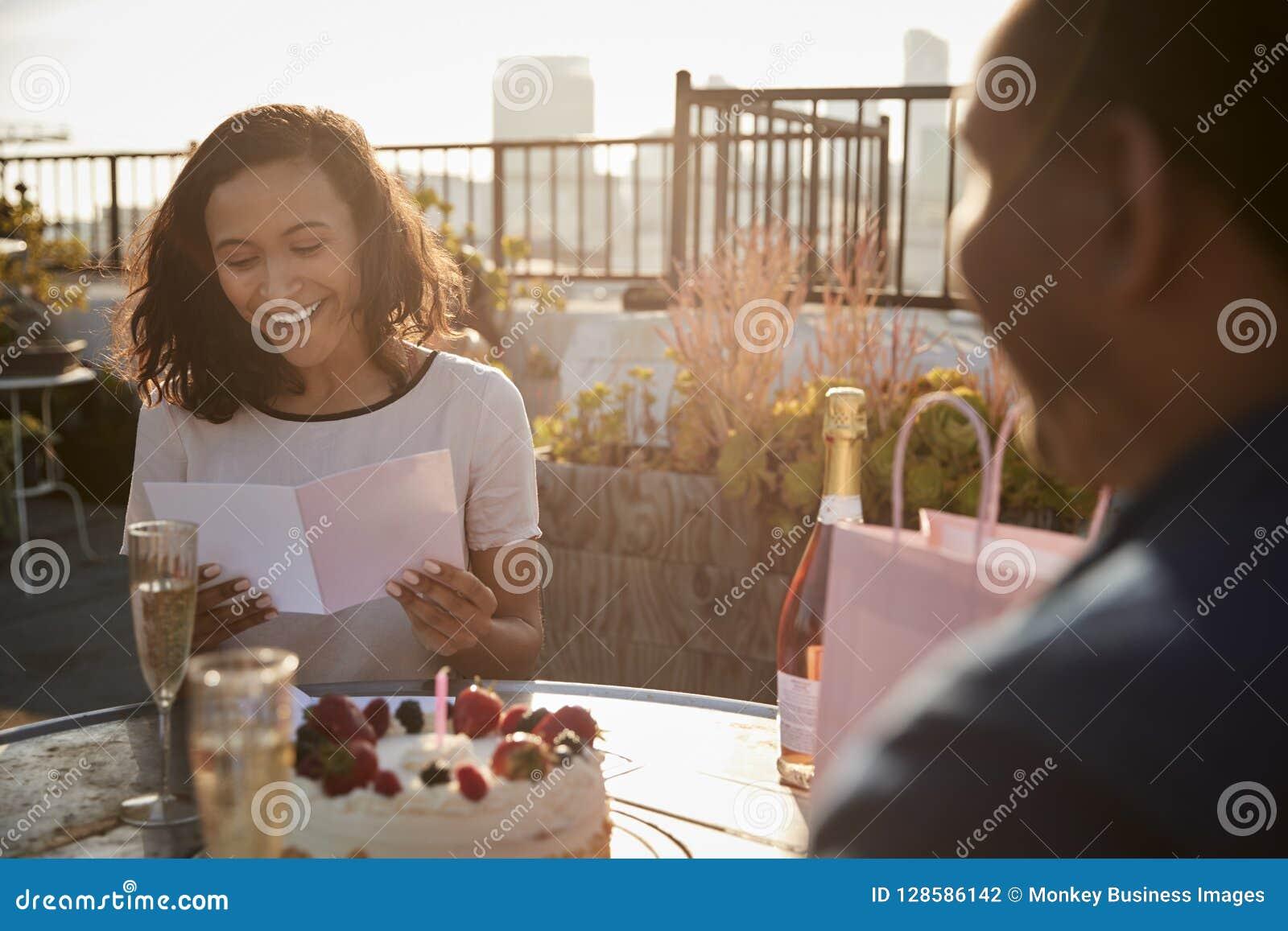 Man som ger kvinnagåvan, och kort, som de firar på takterrass med stadshorisont i bakgrund