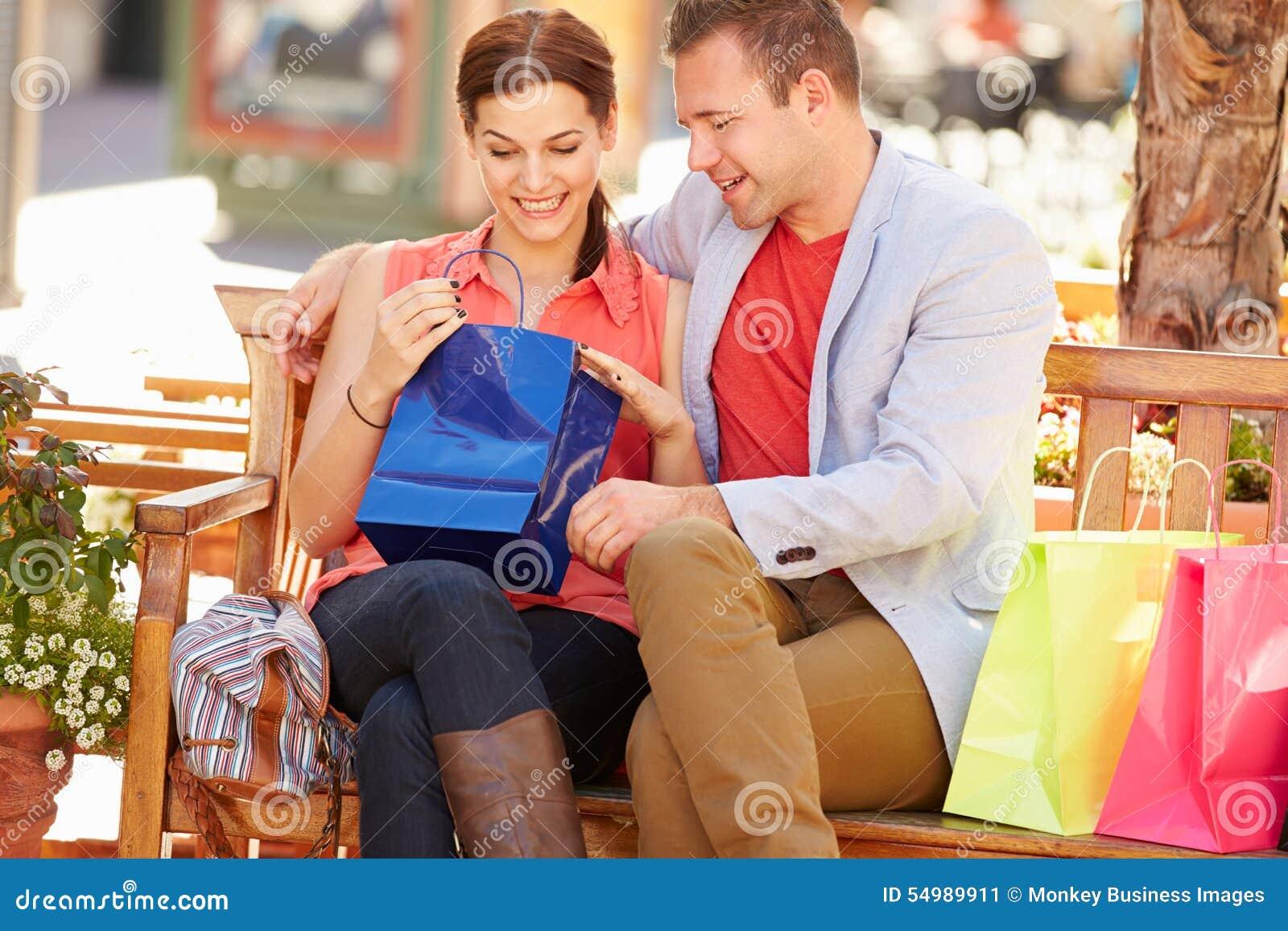 Man som ger kvinnagåvan som dem Sit On Seat In Shopping galleria