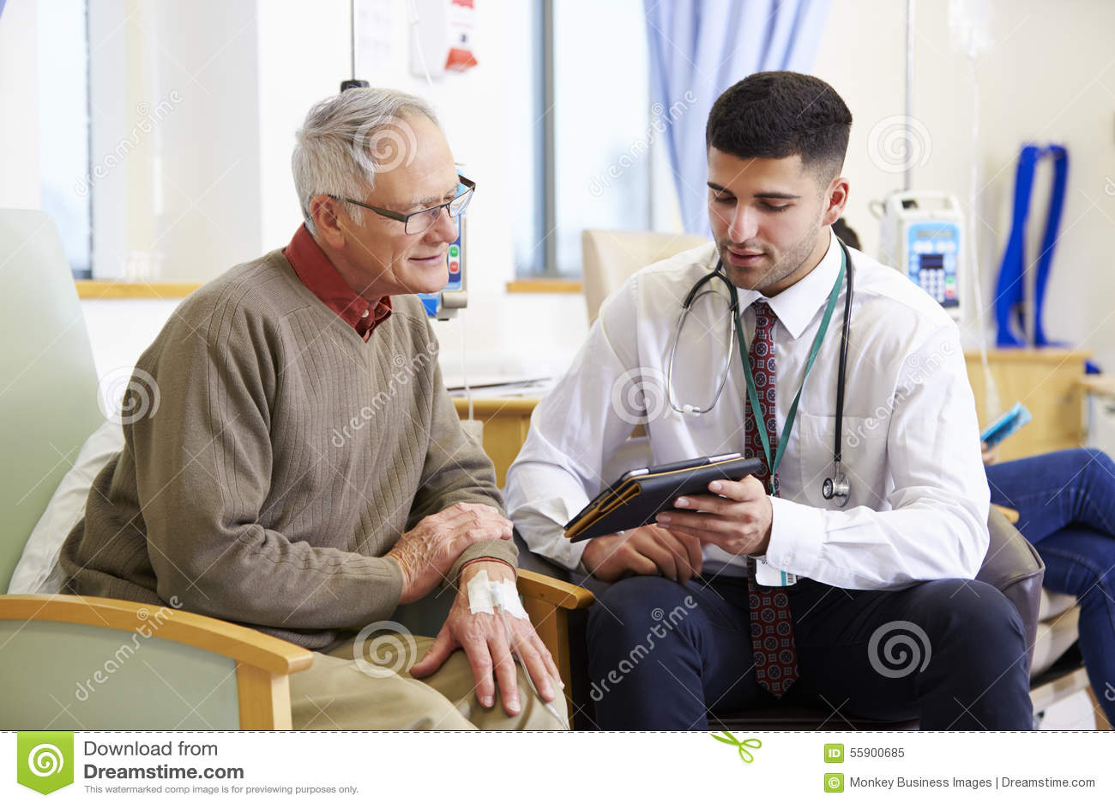 Man som har kemoterapi med doktor Using Digital Tablet