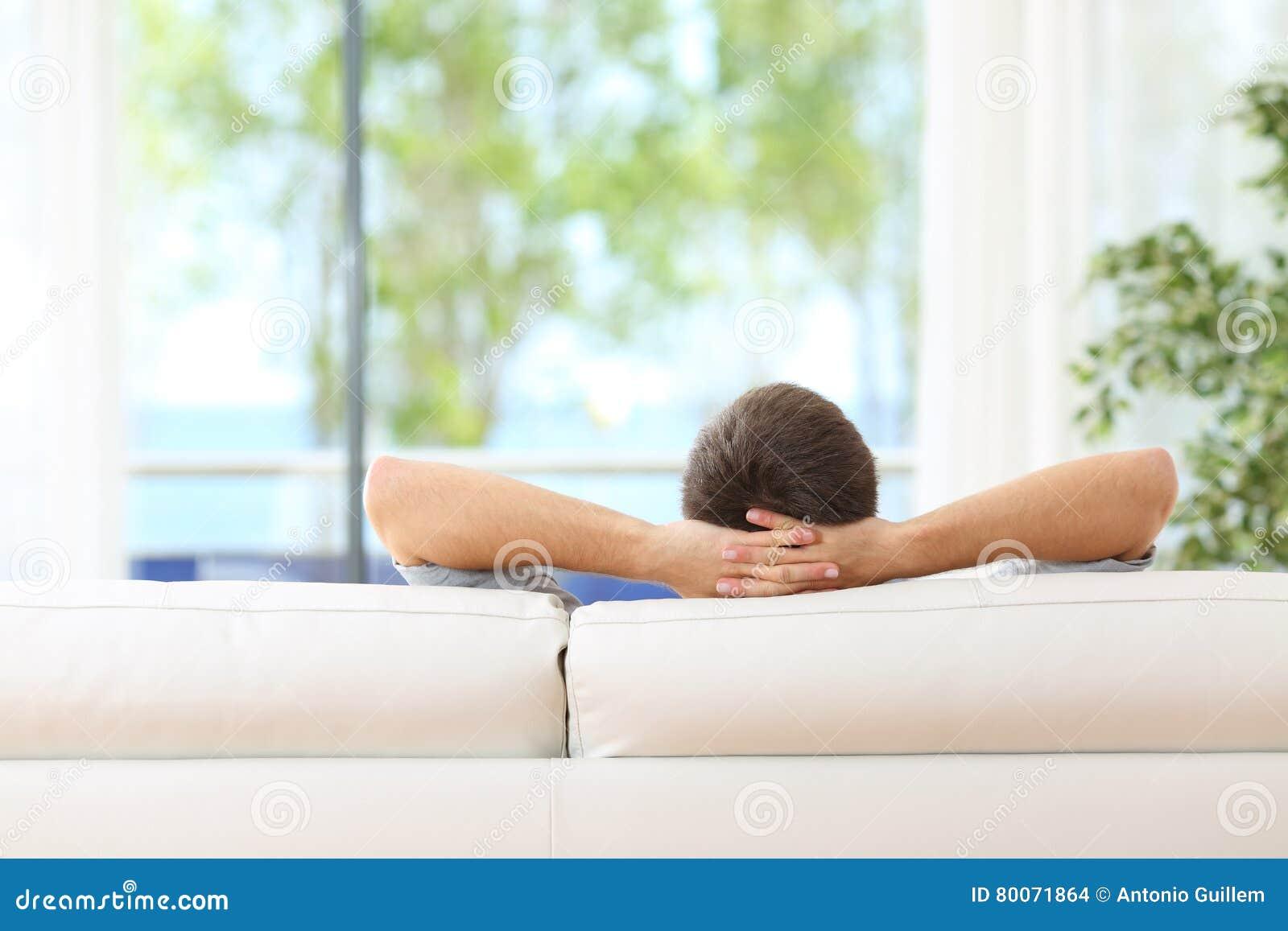 Man som hemma kopplas av på en soffa