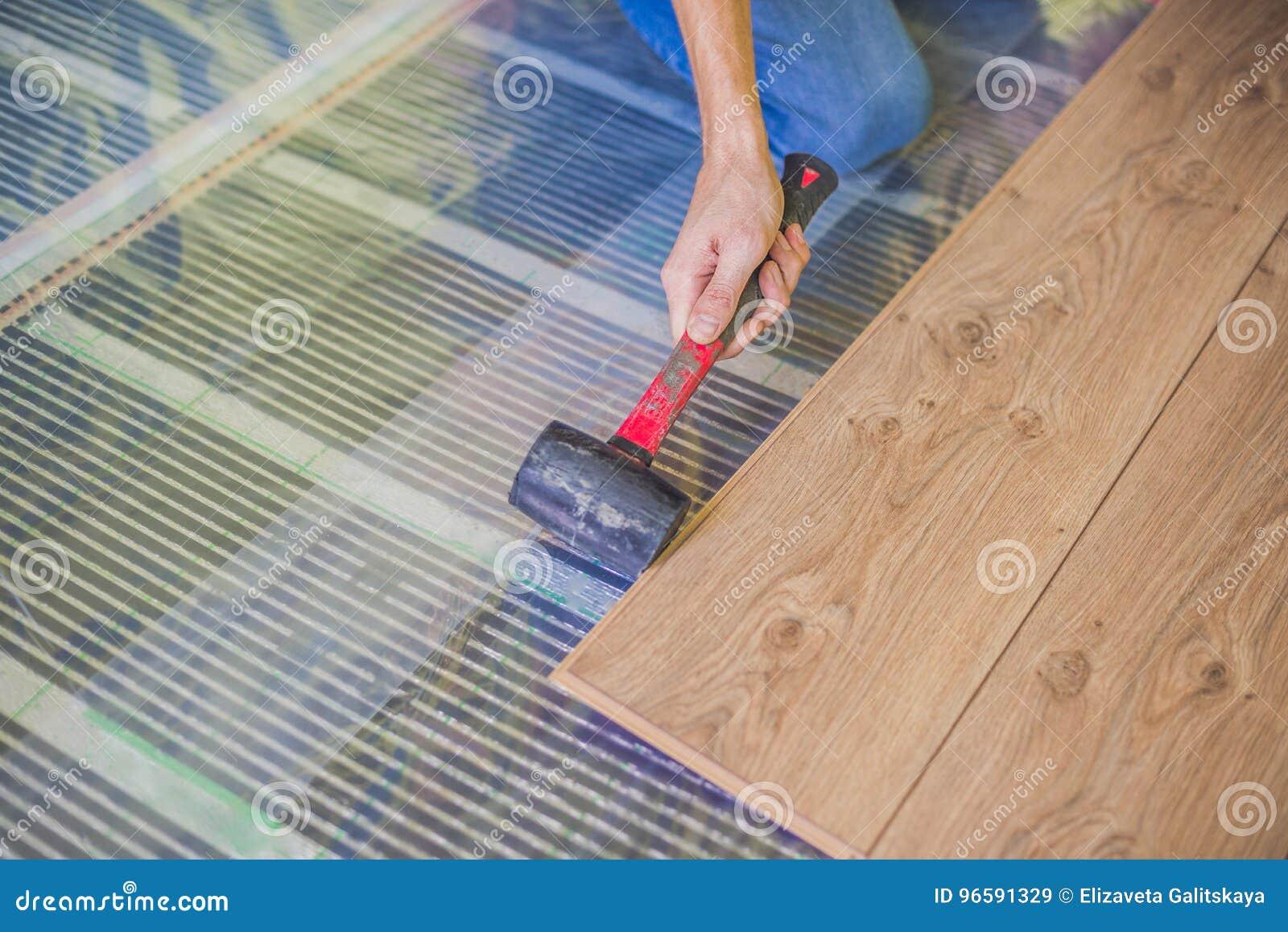 Man som installerar den nya trälaminatdurken infrarött golvuppvärmningsystem under laminatgolv