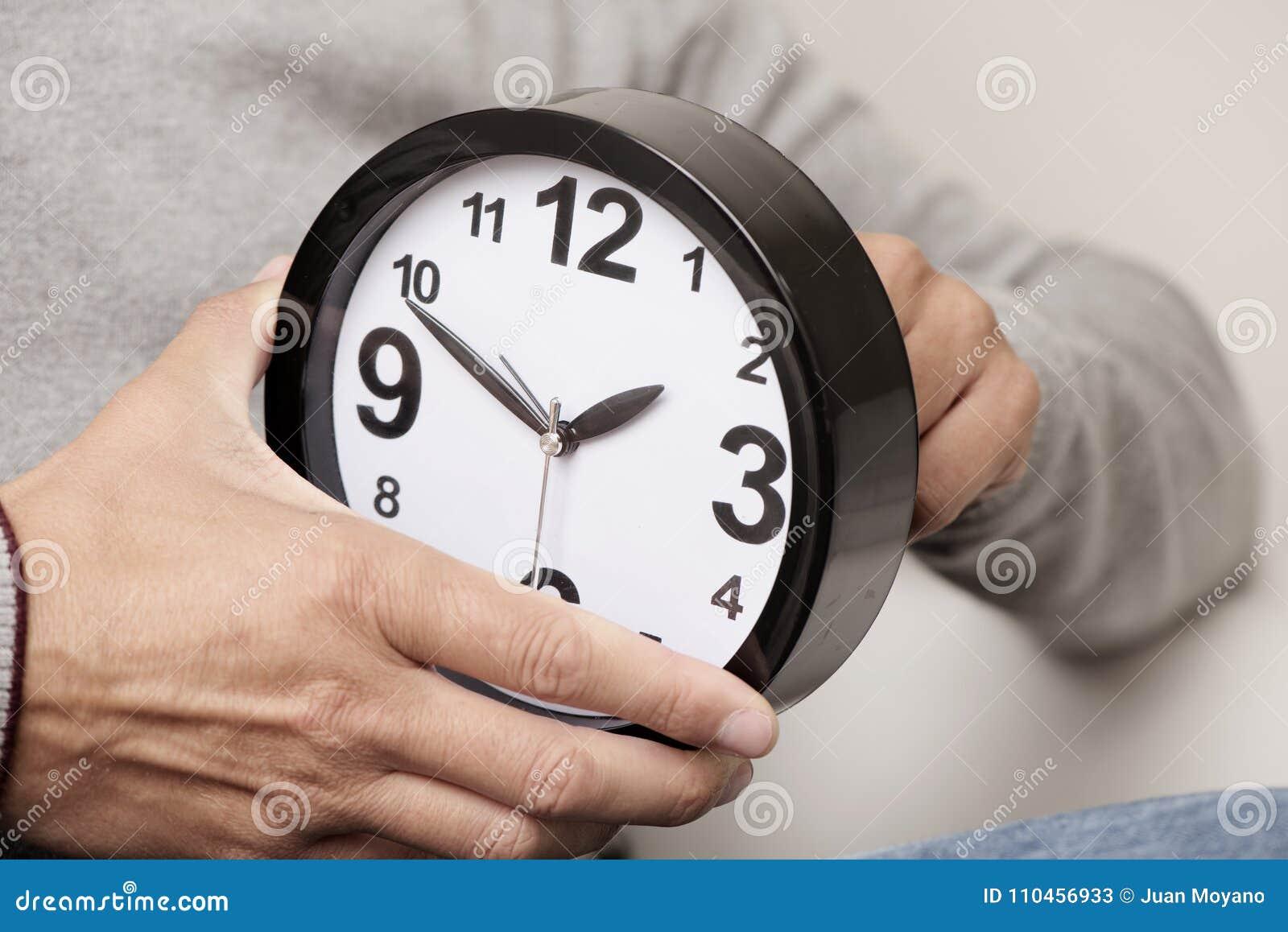 Man som justerar tiden av en klocka