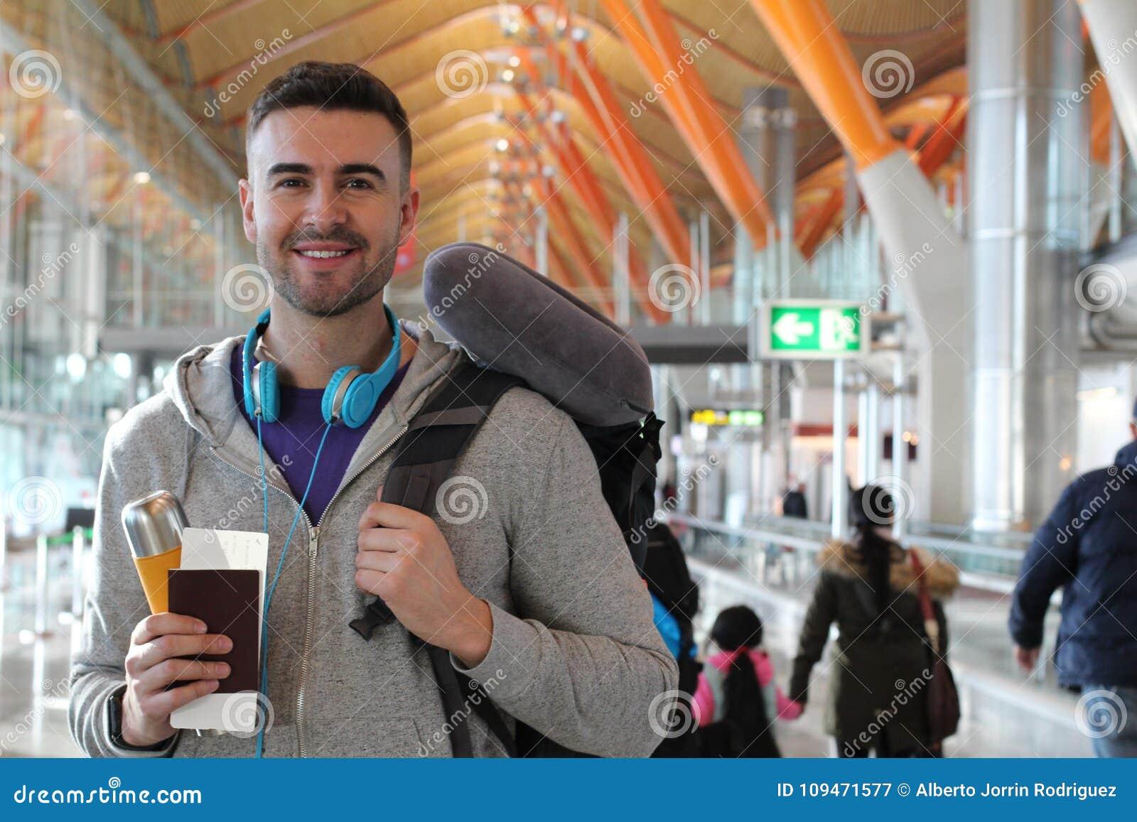 Man som ler i fullsatt flygplats