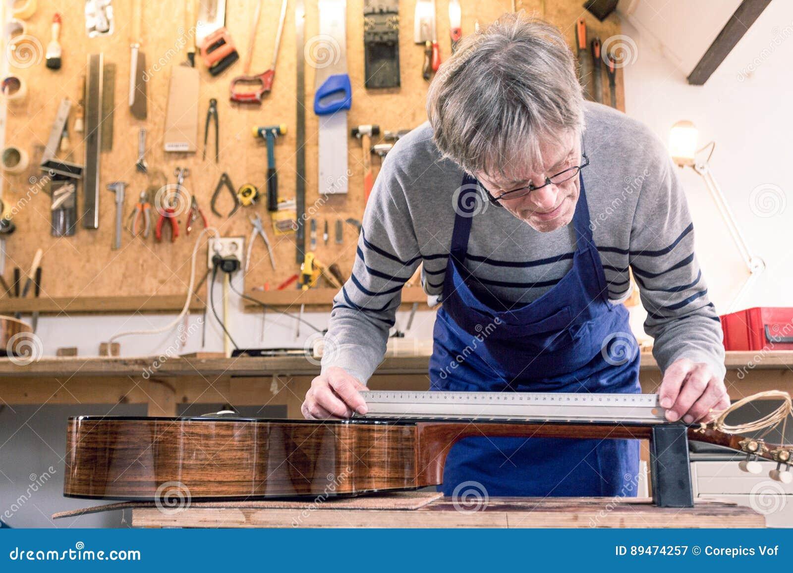 Man som mäter halsen av en gitarr