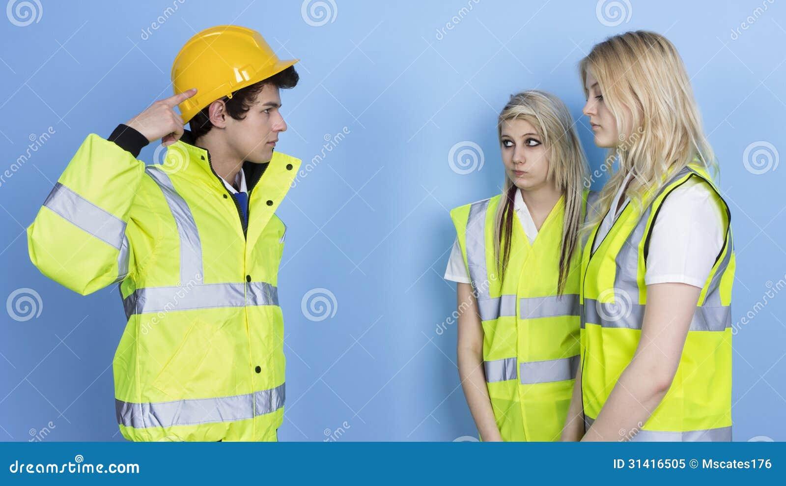 Man som ropar till den kvinnliga arbetaren för att inte bära den hårda hatten