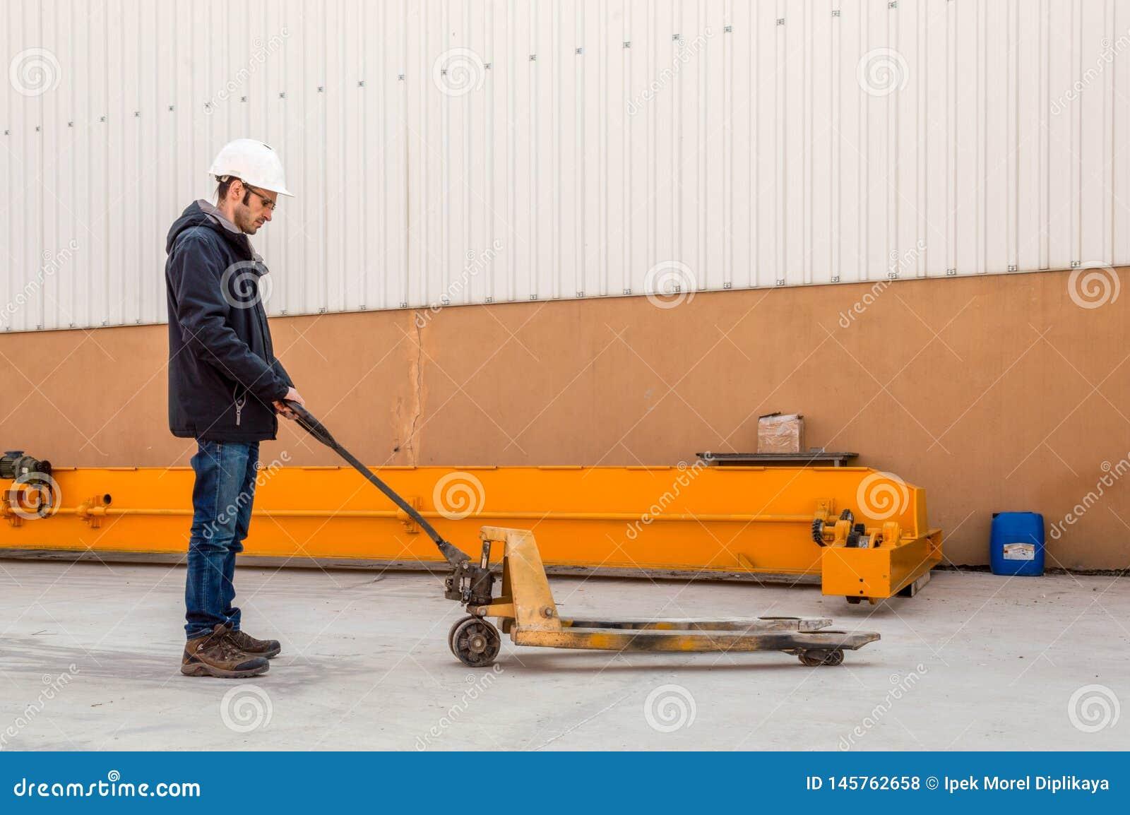 Man som rymmer tom manuell utrustning för lastbil för gaffeltruckpalettutmatningsfack i efterbehandlaren