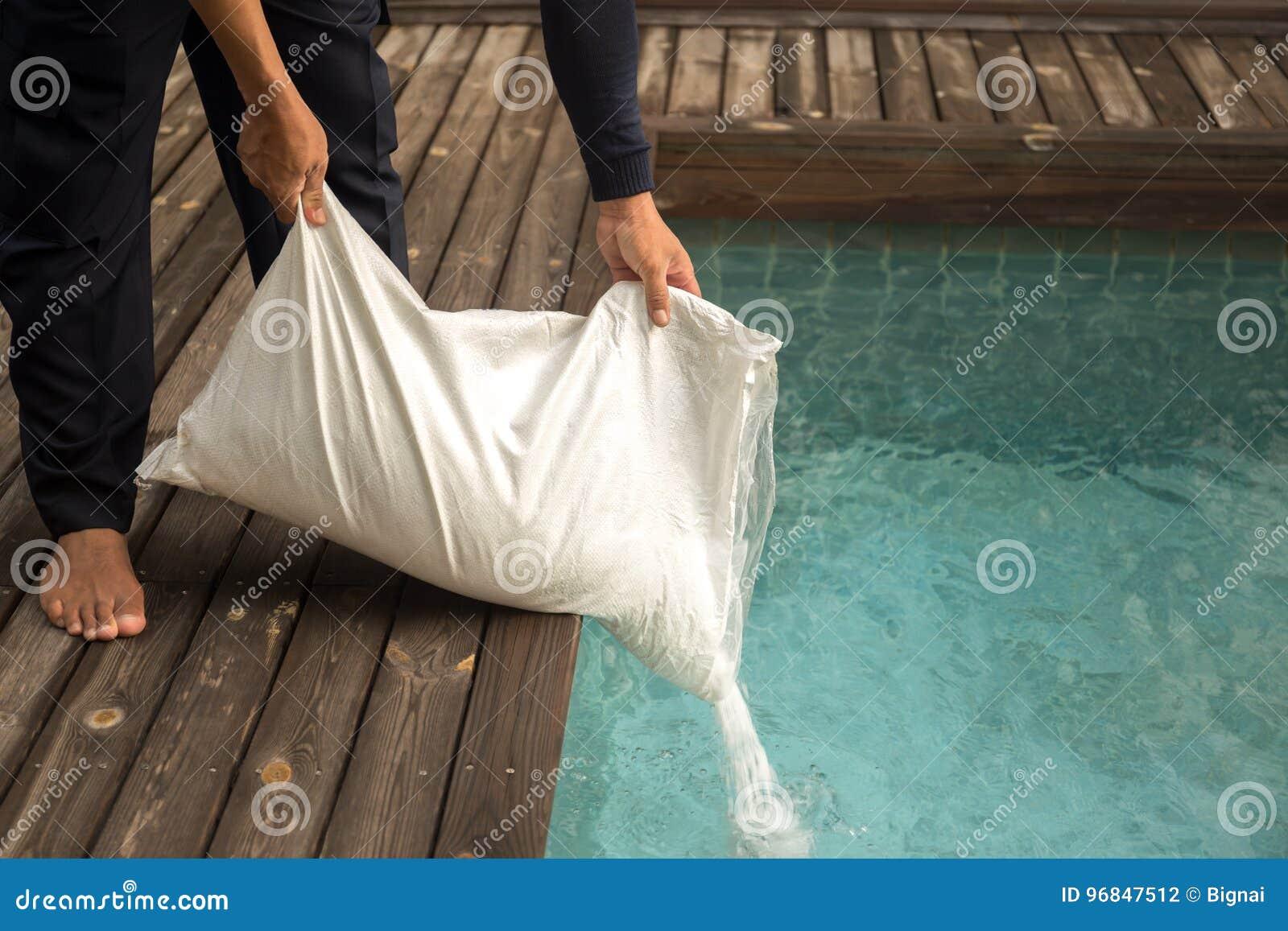 Man som sätter den salta chlorinatoren för behandlingvatten i simningbajs