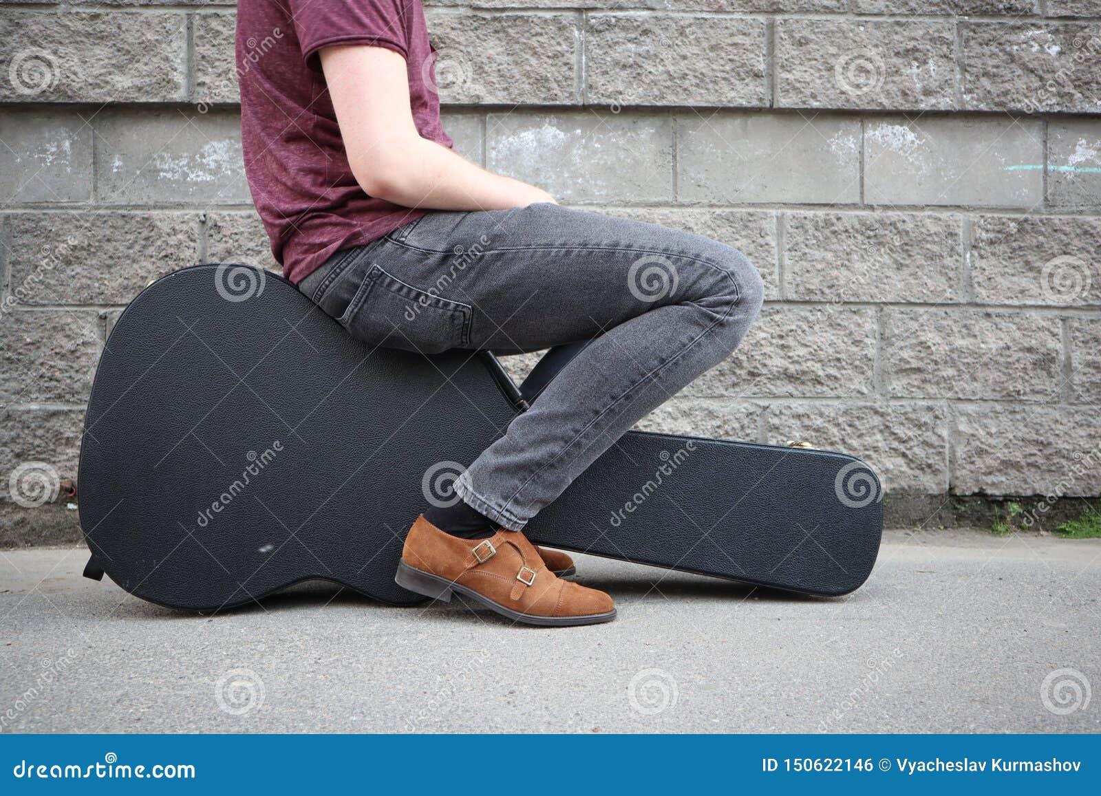 Man som sitter på ett svart gitarrfall H?rt fall f?r elektrisk gitarr