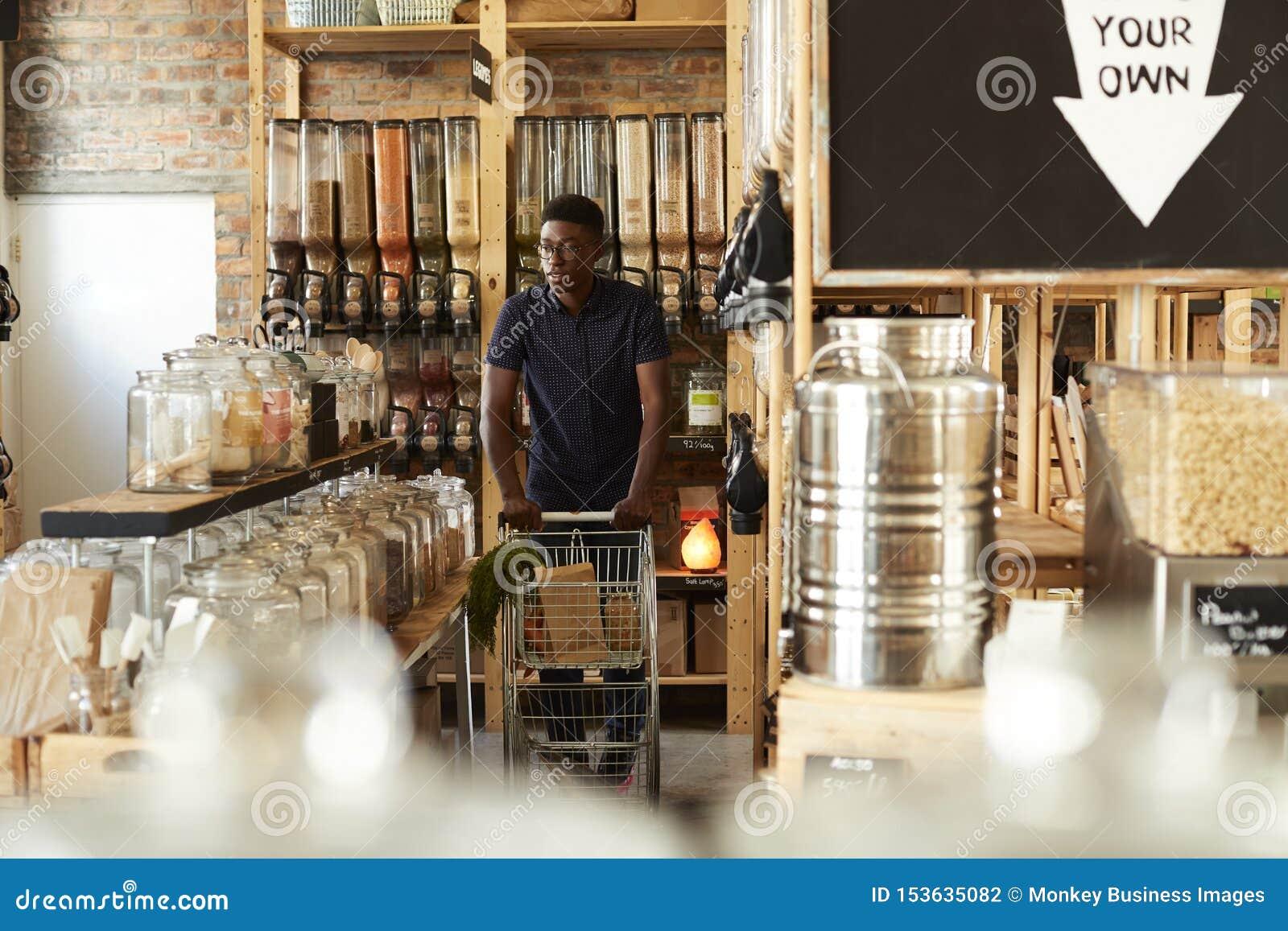 Man som skjuter shoppa spårvagnen till och med avsnitt för torkat gods av den hållbara plast- fria livsmedelsbutiken