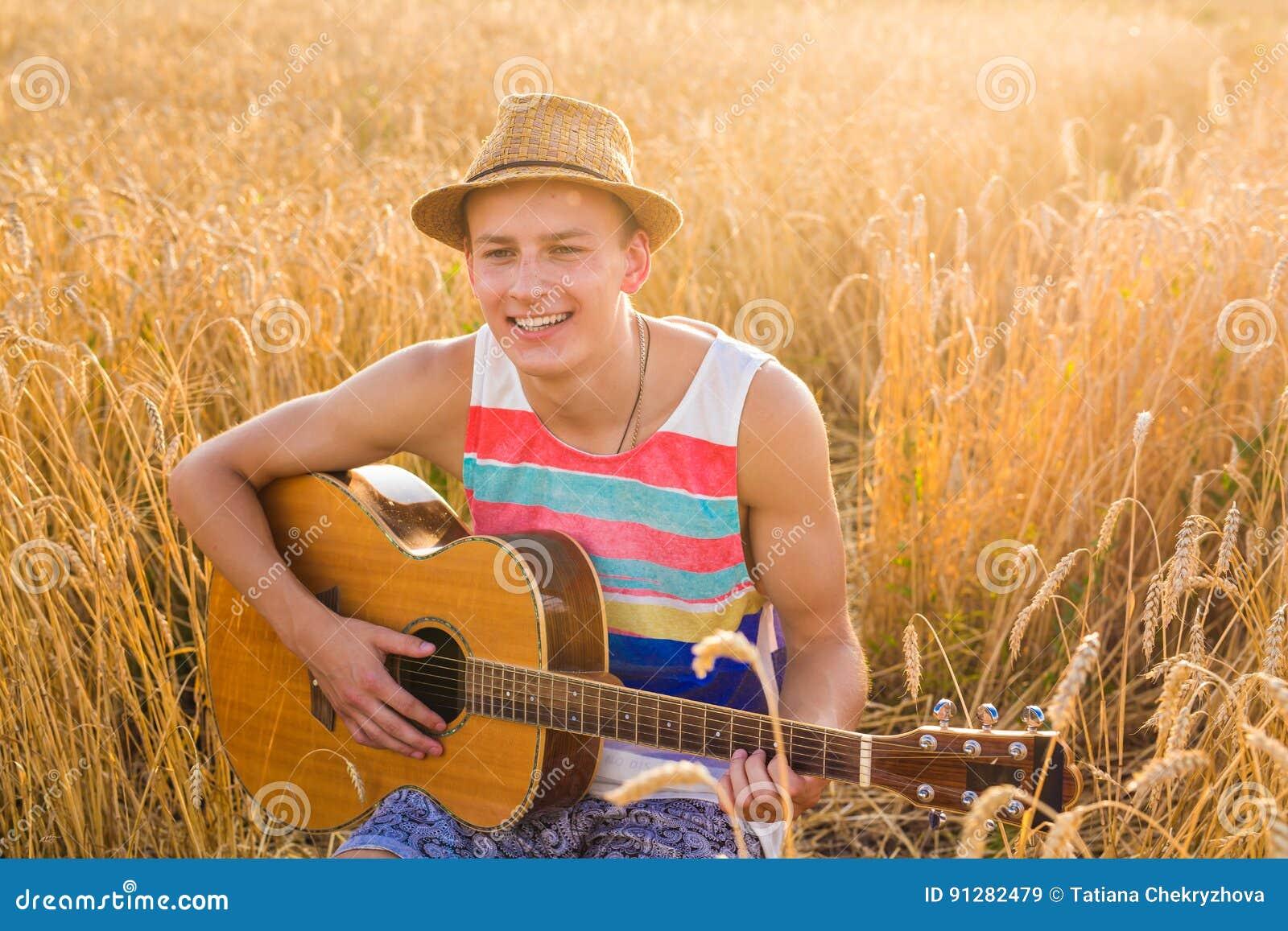 Man som spelar utomhus den akustiska gitarren
