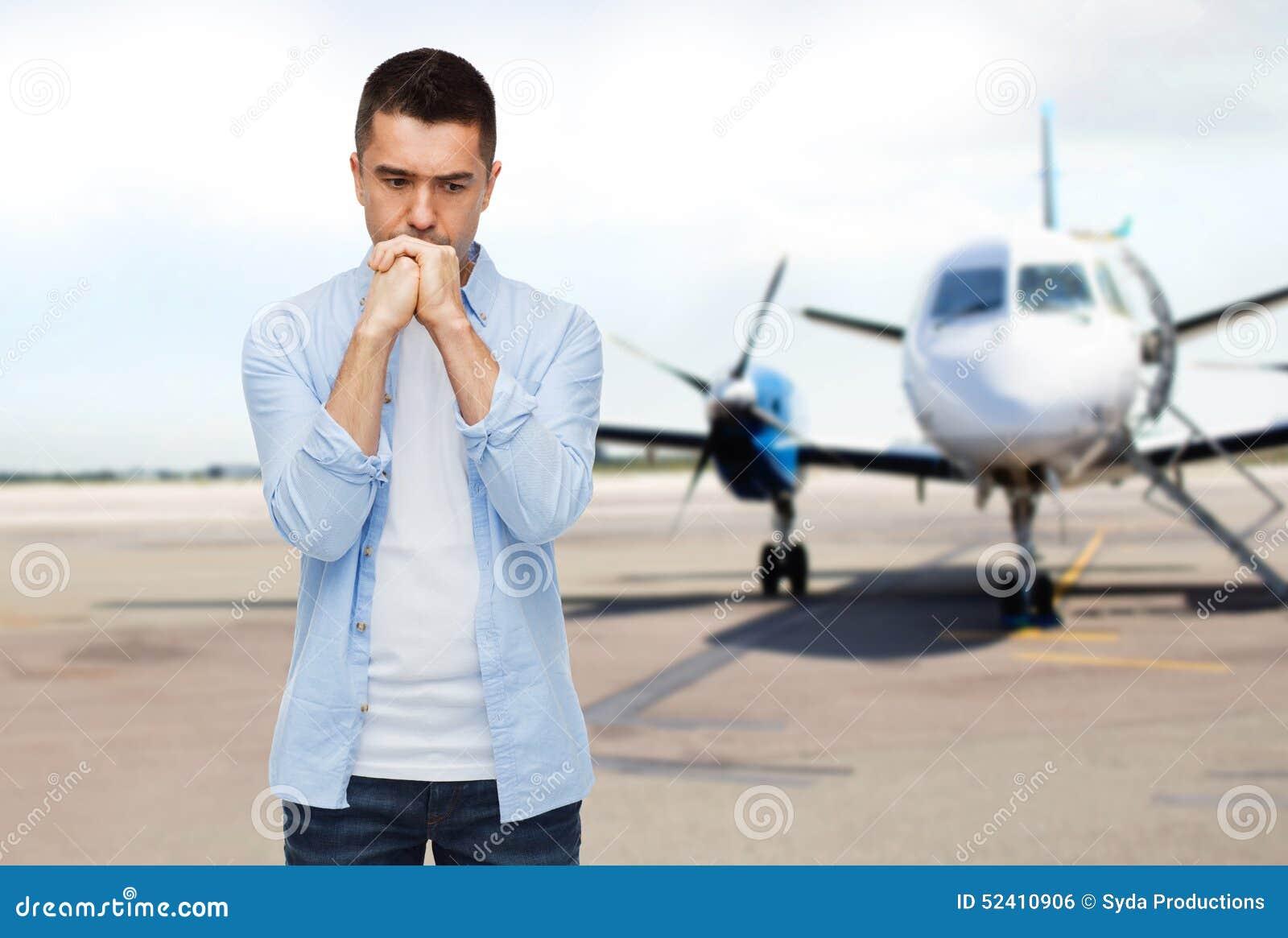 Man som tänker över flygplanet på landningsbanabakgrund