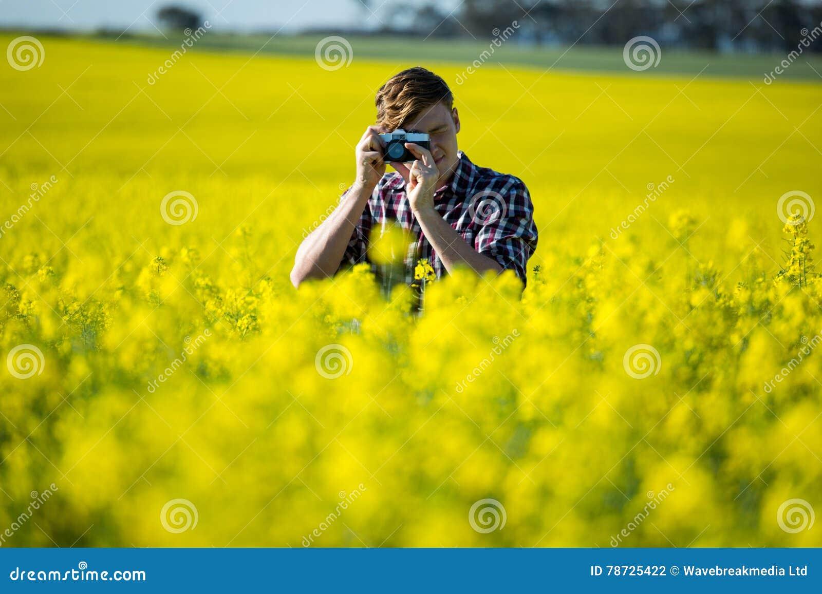 Man som tar bilden från kamera i senapsgult fält