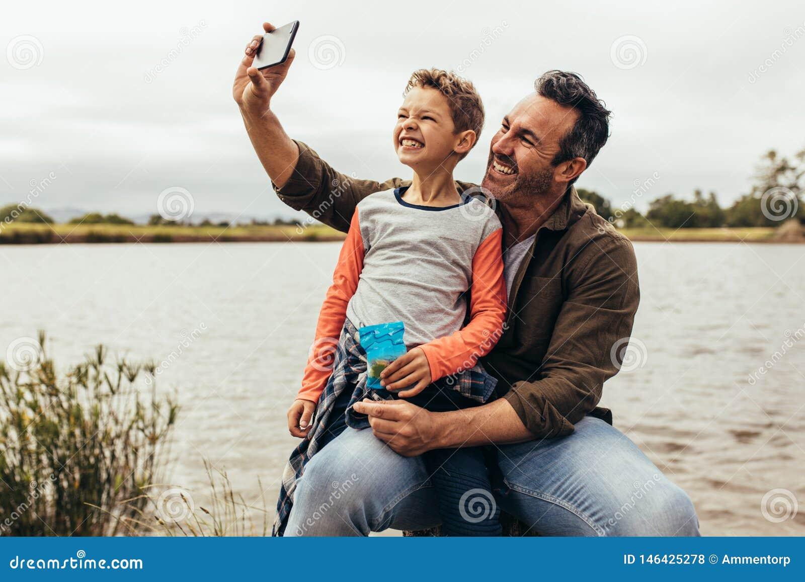 Man som tar en selfie genom att använda en mobiltelefon