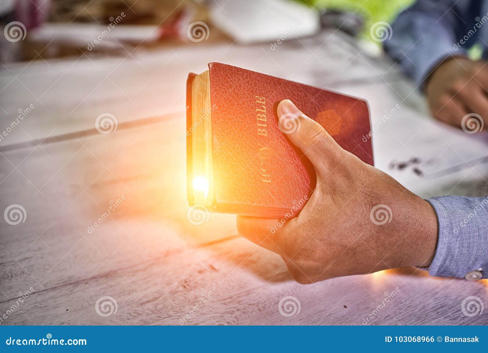 Man som trycker på den heliga bibeln