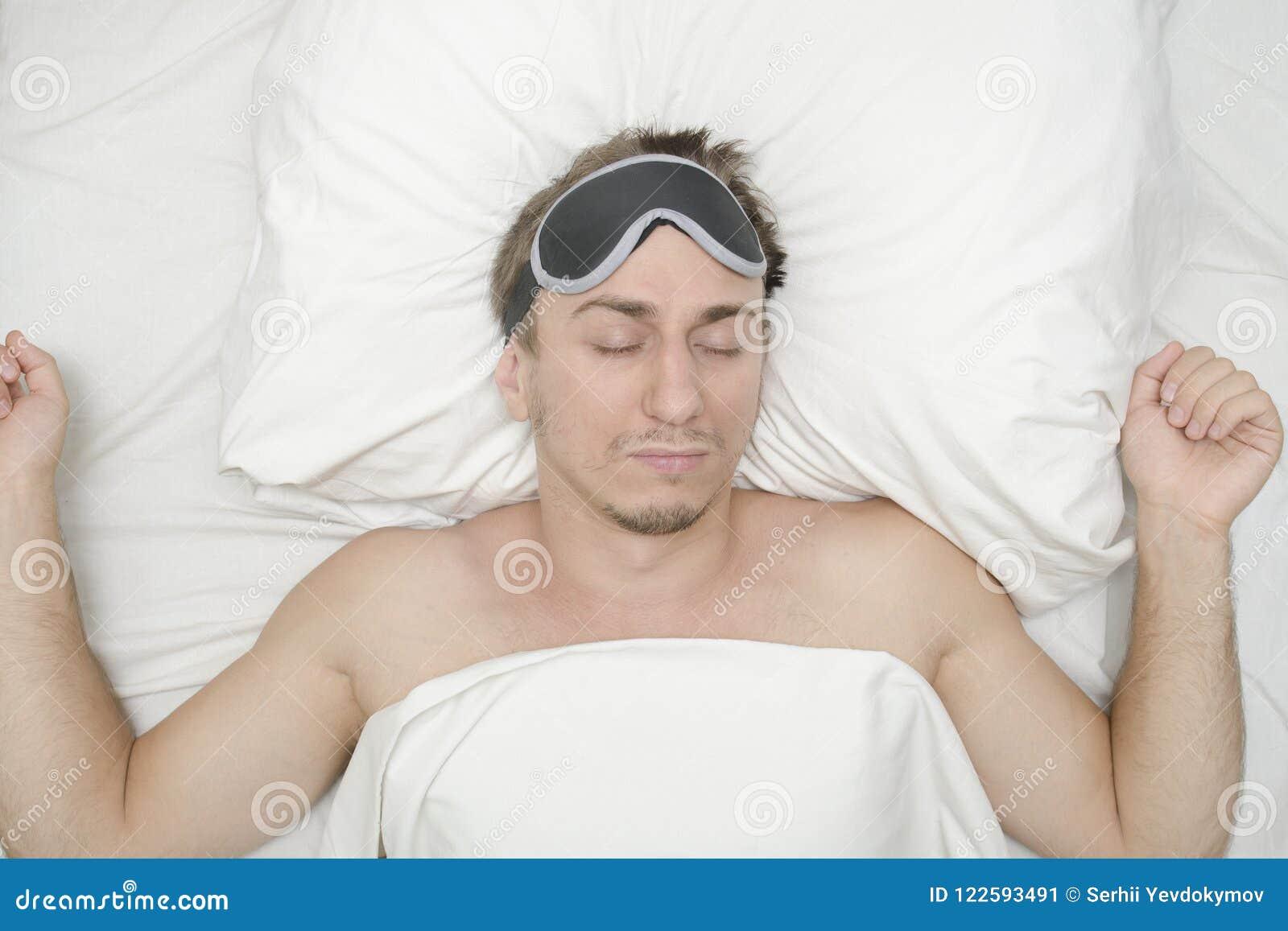 Man som vilar i en maskering för sömn Skäggstubb på hans framsida tröttad man