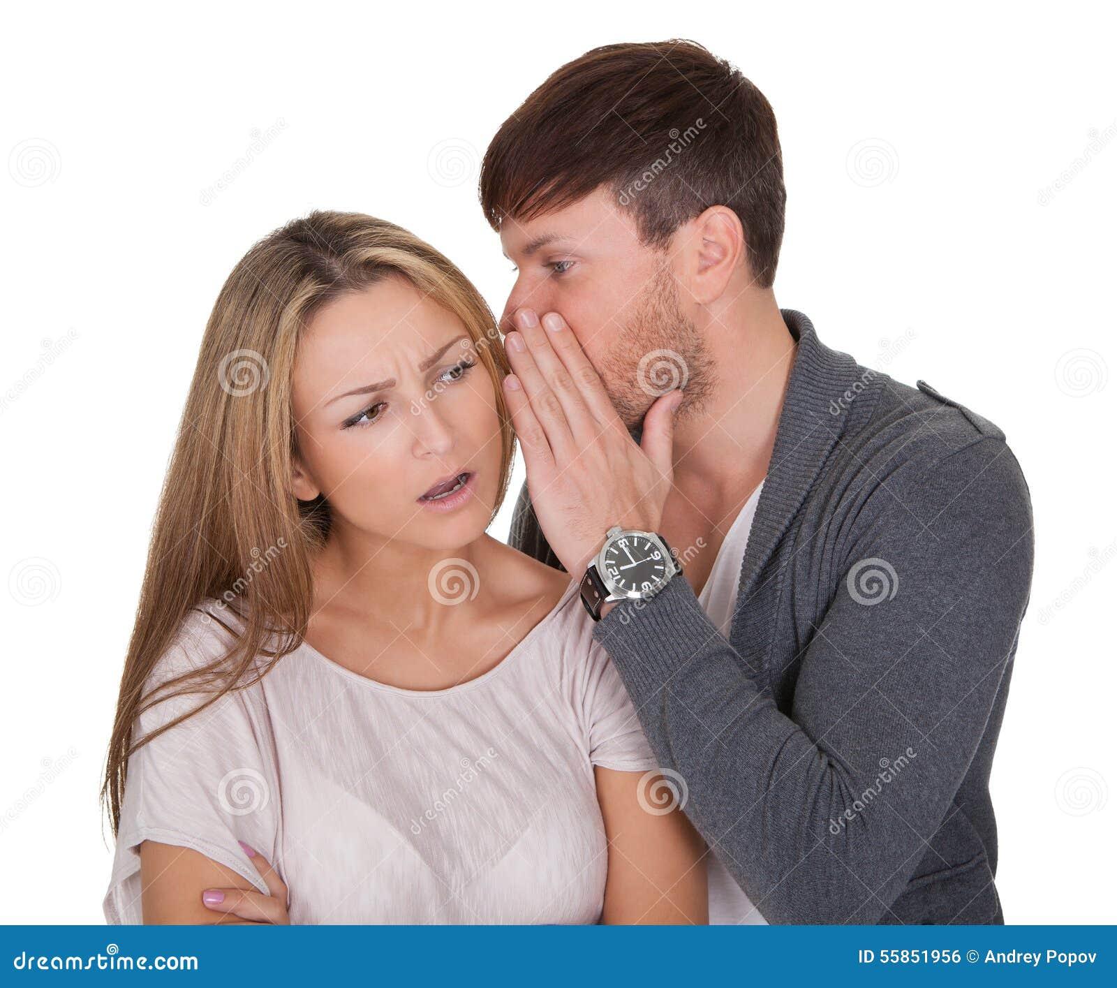 Man som viskar i en kvinnas öra