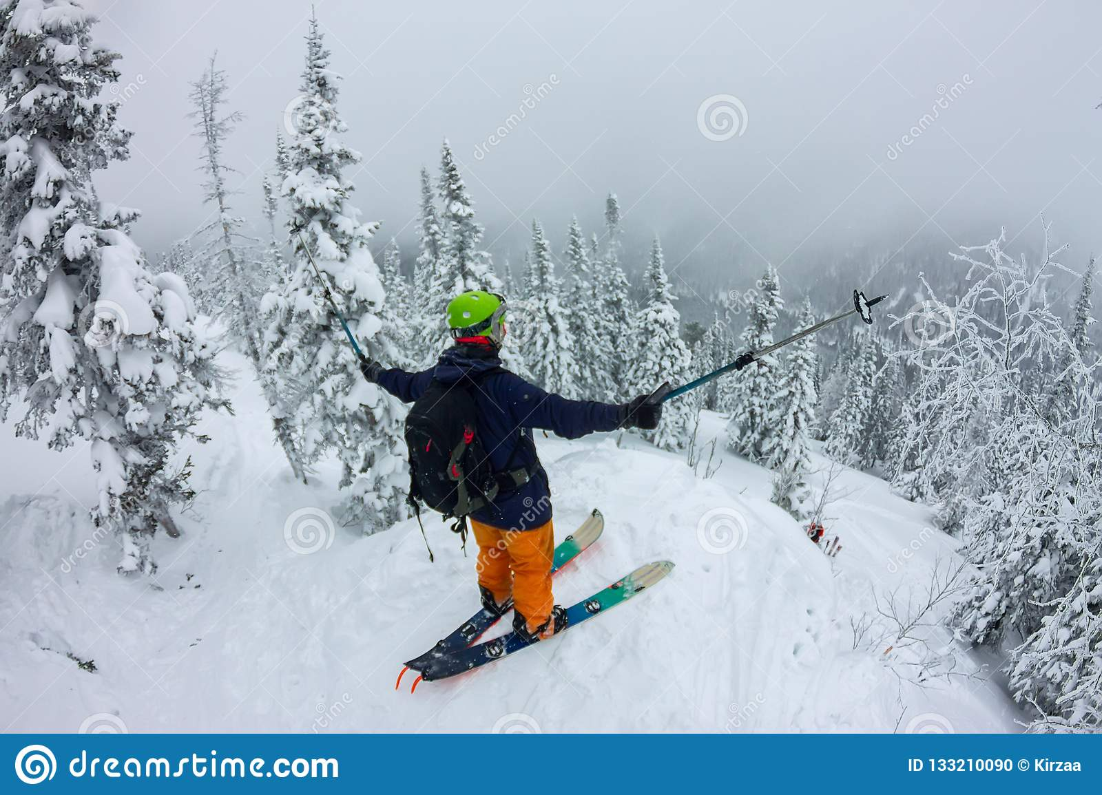 Man splitboard freerider standing at top of ridge. Ski touring in mountains, winter freeride extreme sport