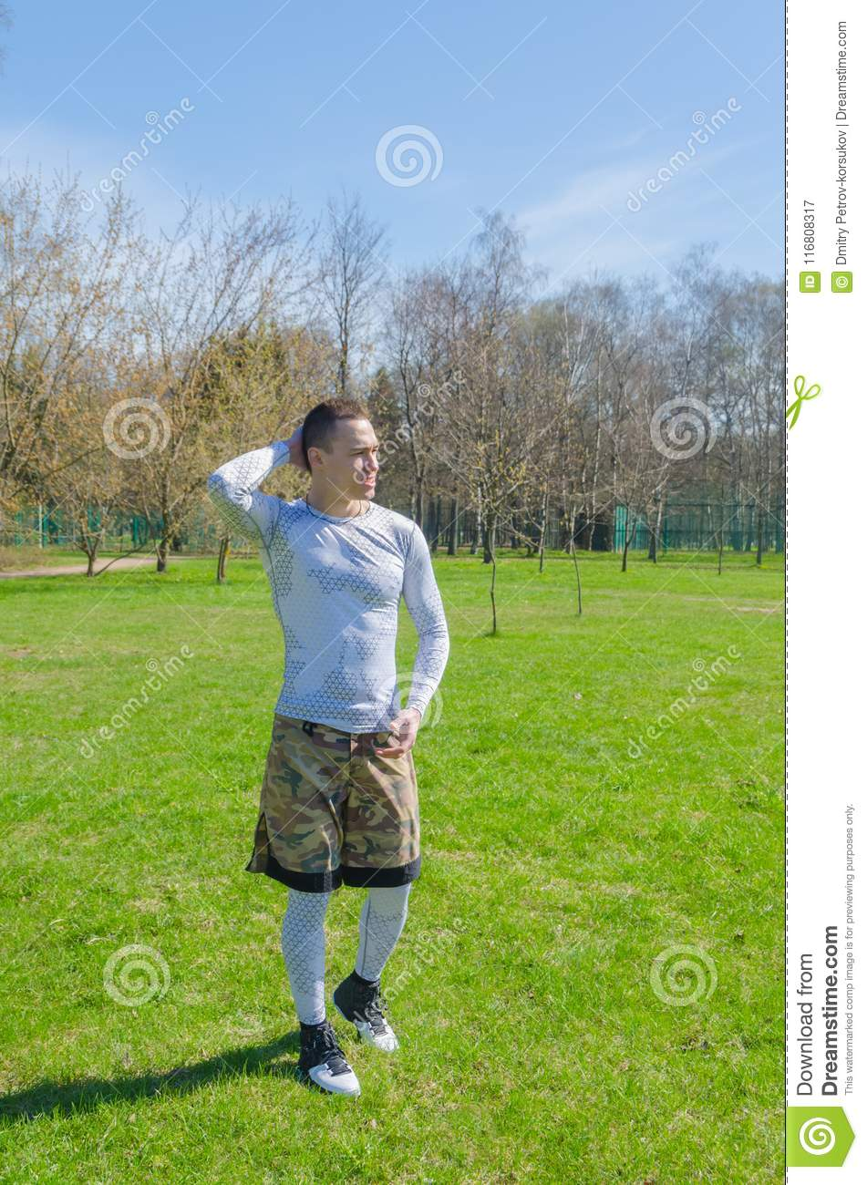 5b1507f5b91 Strong man in white sports clothes in summer