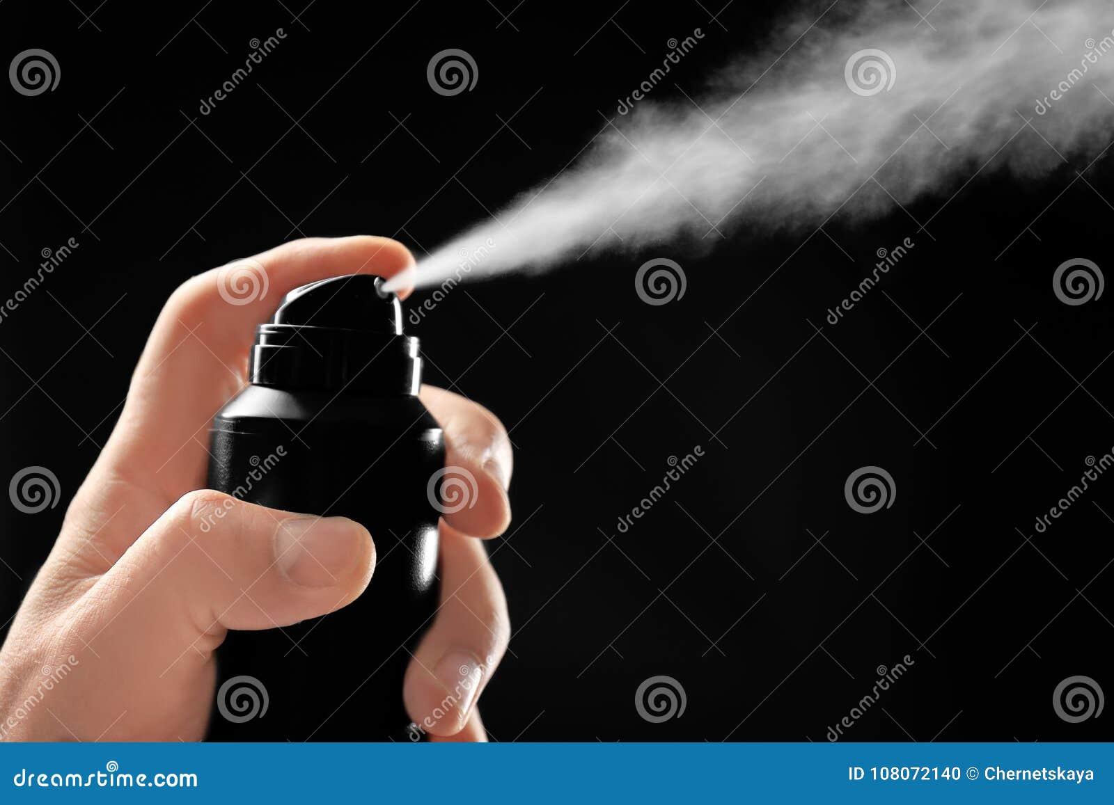 Man spraying deodorant on dark background,