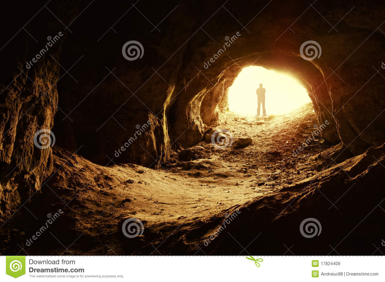 Man standing in front of a cave entrance