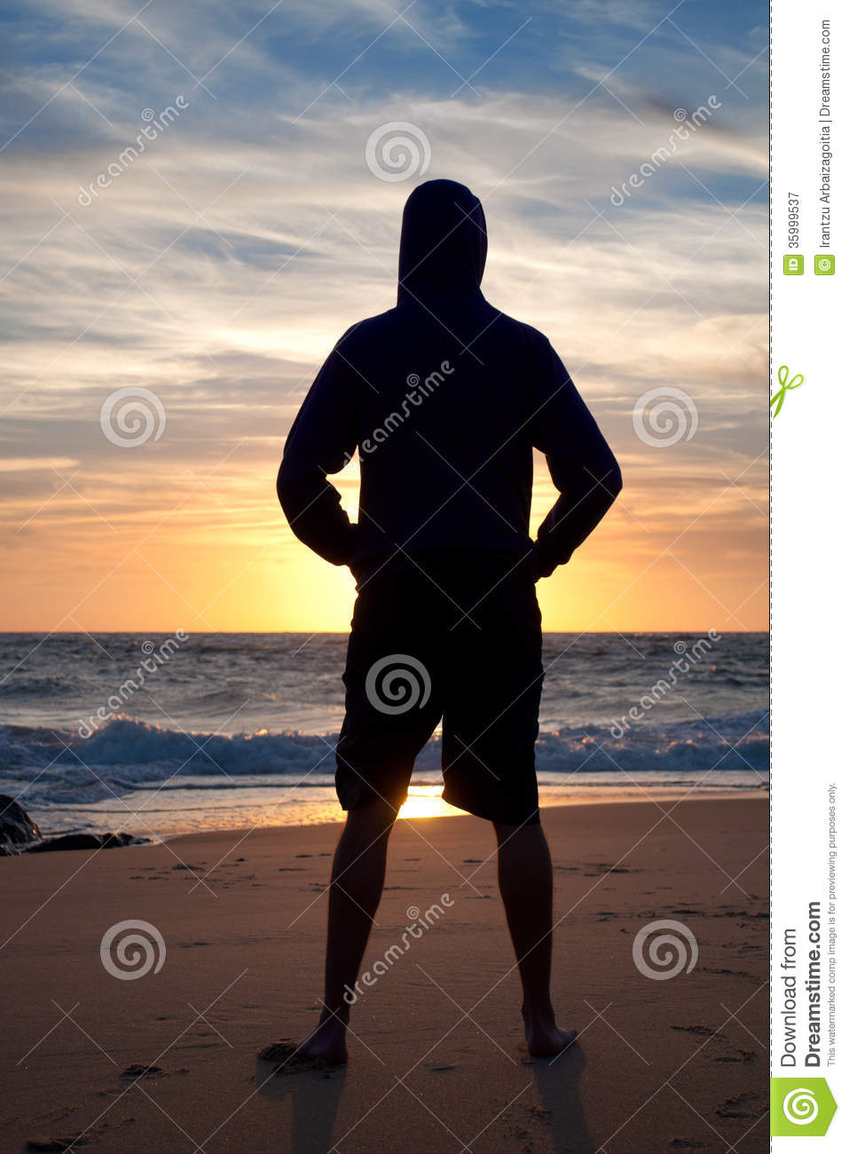 Man Standing Looking At The Sunset In The Beach Stock