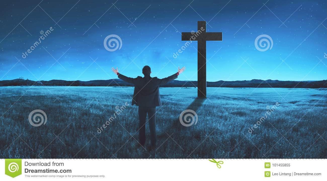 Man standing in the middle of the meadow, praying