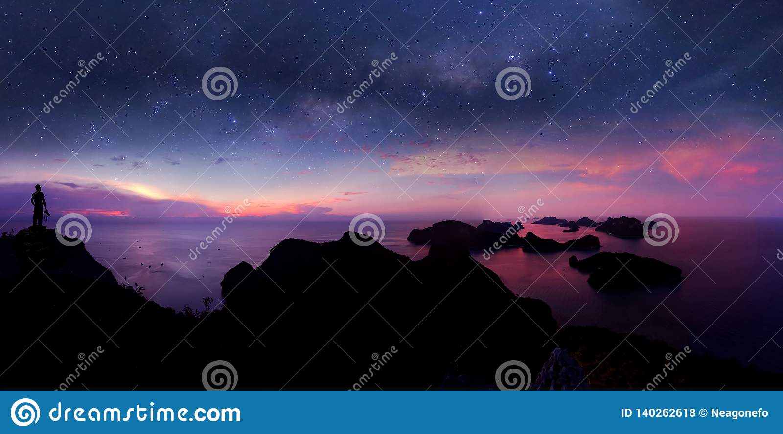 Man standing on the mountain with panorama view and million stars galaxy
