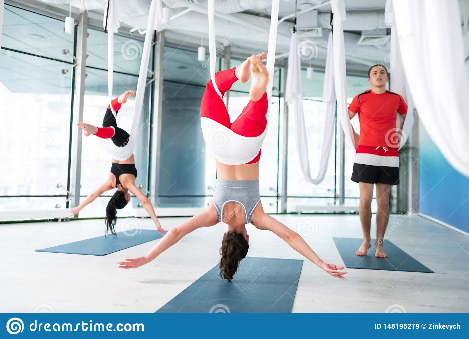 Man Standing Near Friends Practicing Aerial Yoga Poses ...
