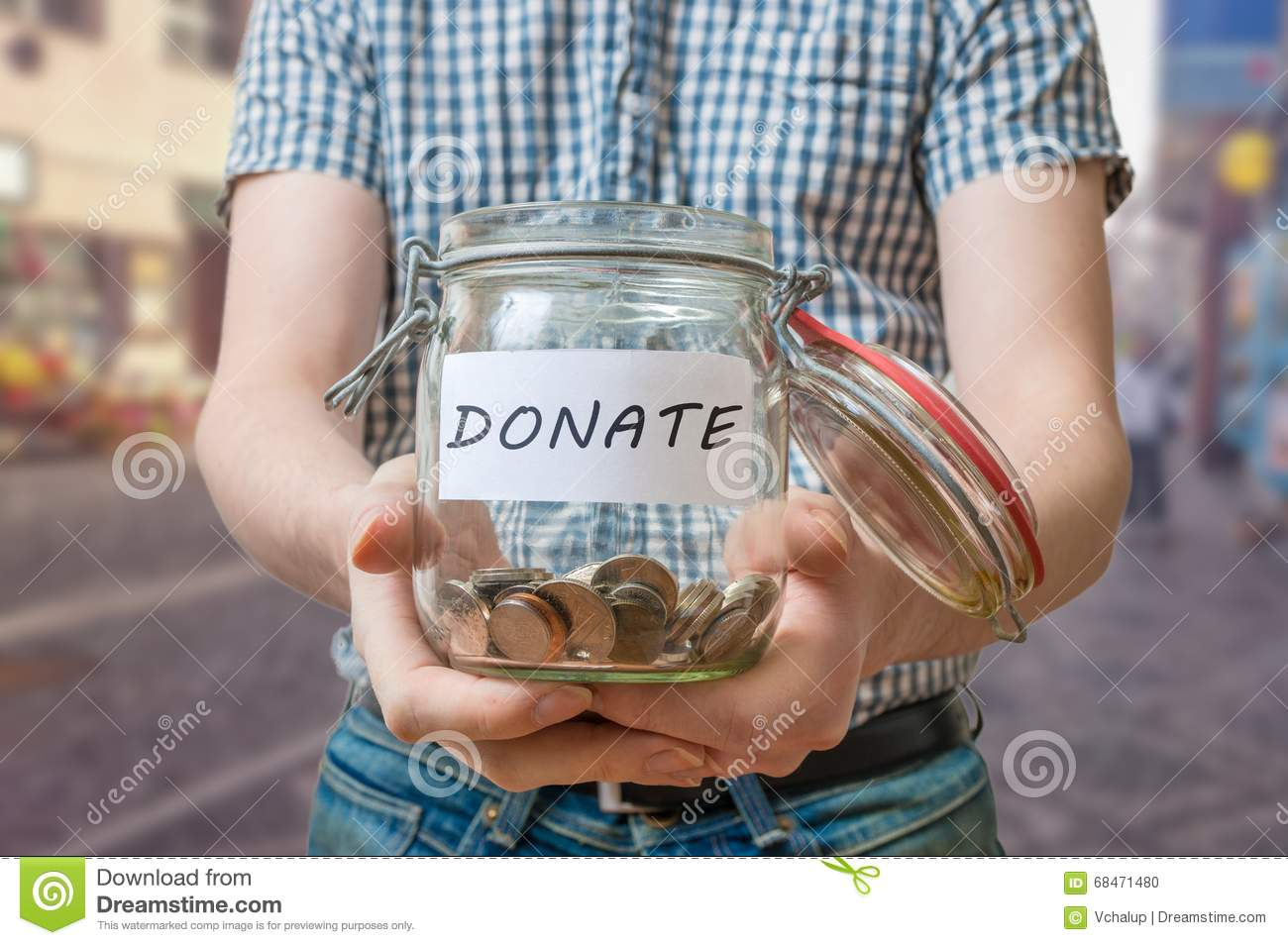 Man standing on street is collecting donations in jar
