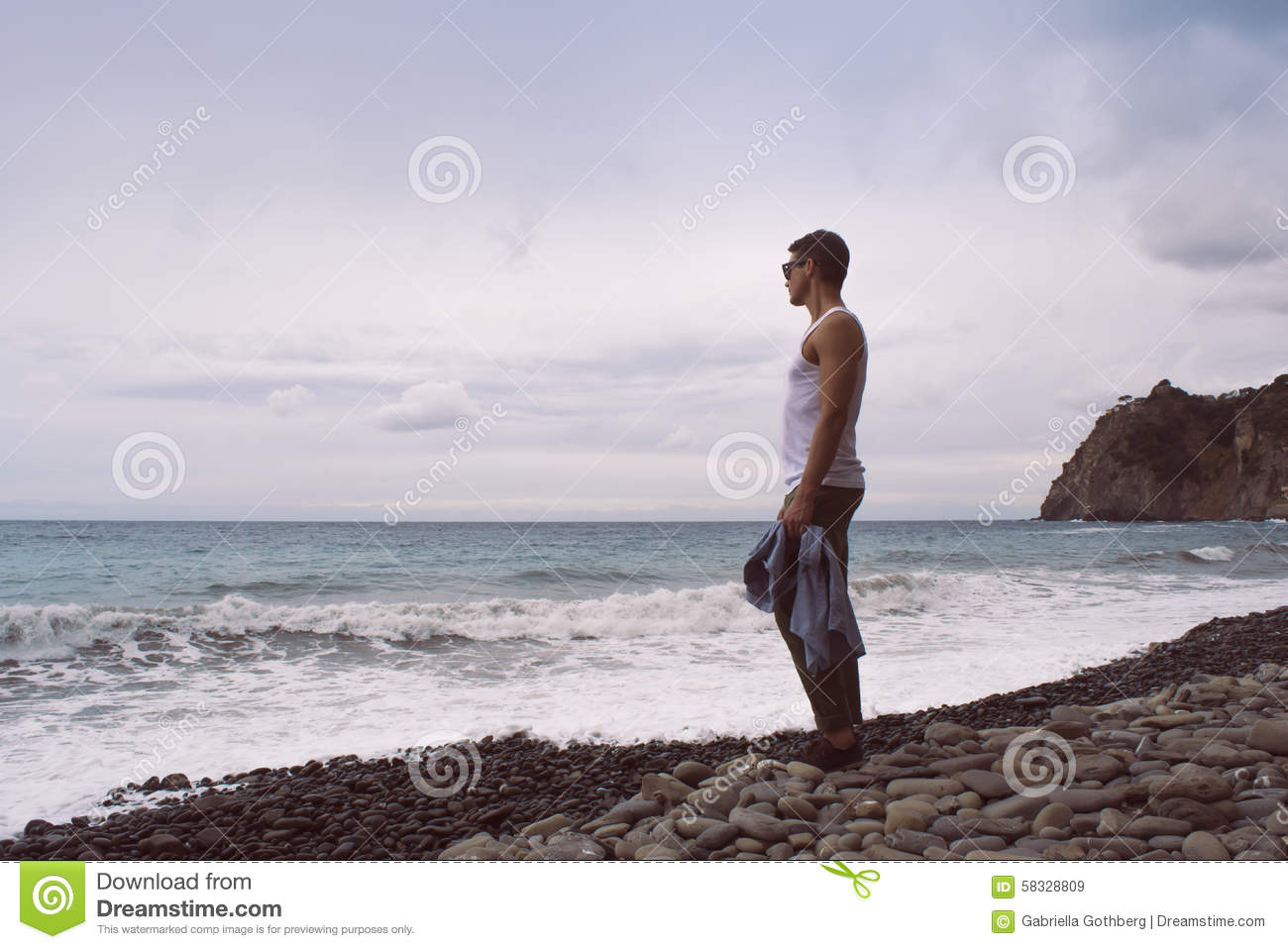 Man standing by the waves of the ocean on a rocky beach.
