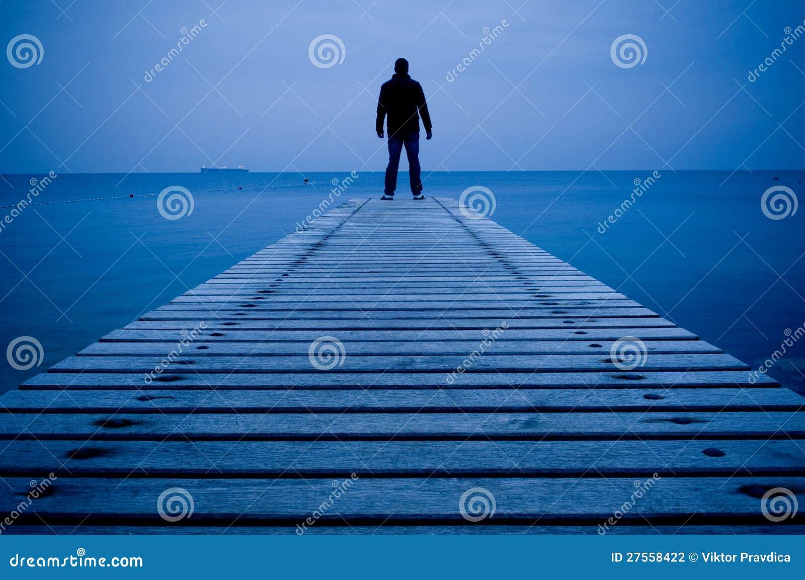 Man standing on a wooden pier