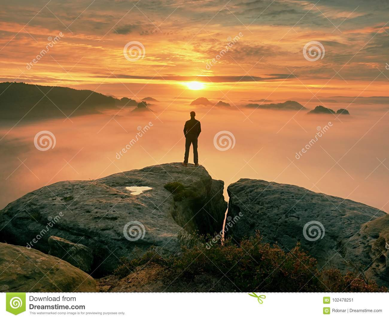 Man stands alone on the peak of rock. Hiker watching to autumn Sun at horizon . Beautiful moment the miracle of nature. Colorful
