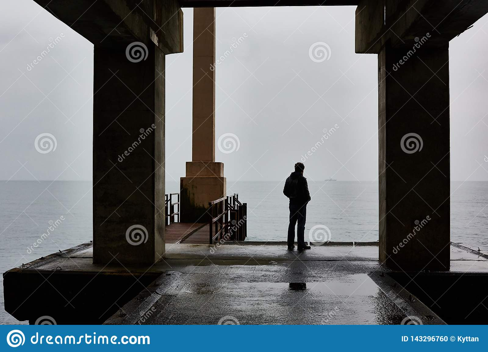 Man stands alone on a pier of sea in bad weather. Foggy air
