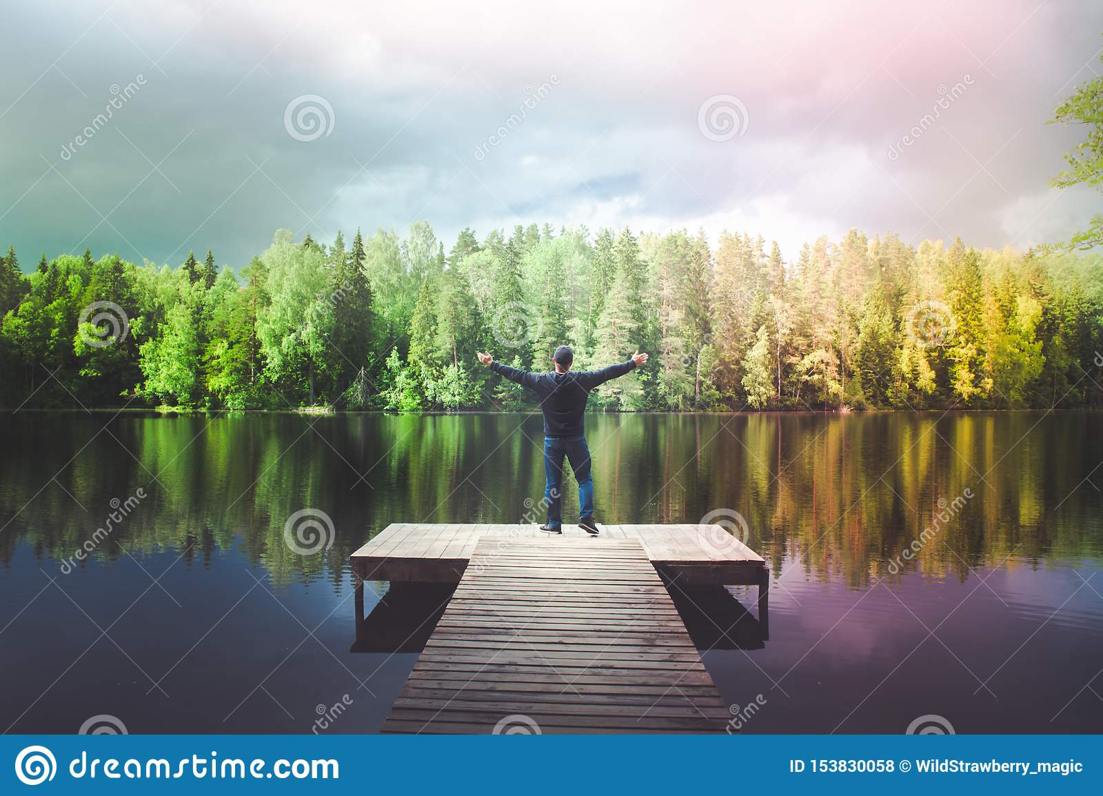 Man Stands On The Pier Of A Beautiful Lake Young Man
