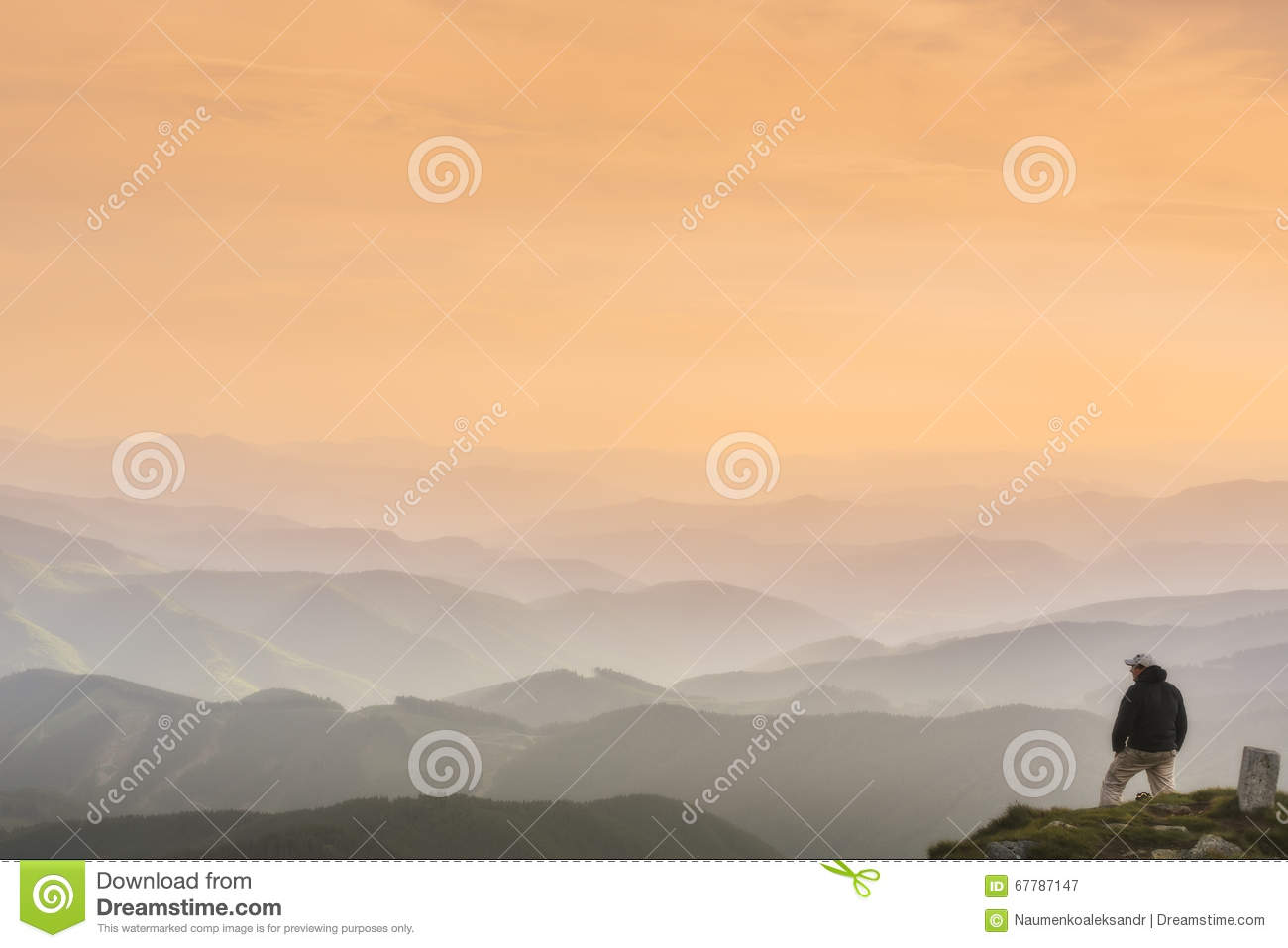 A Man Stands On Top Of A Mountain And Looks Into The Distanceon - This man hikes up the transylvanian mountains every morning to photograph sunrise