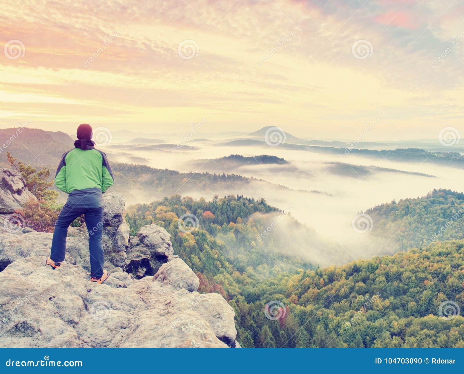Man stay on rocky peak within daybreak and watch over misty landscape.