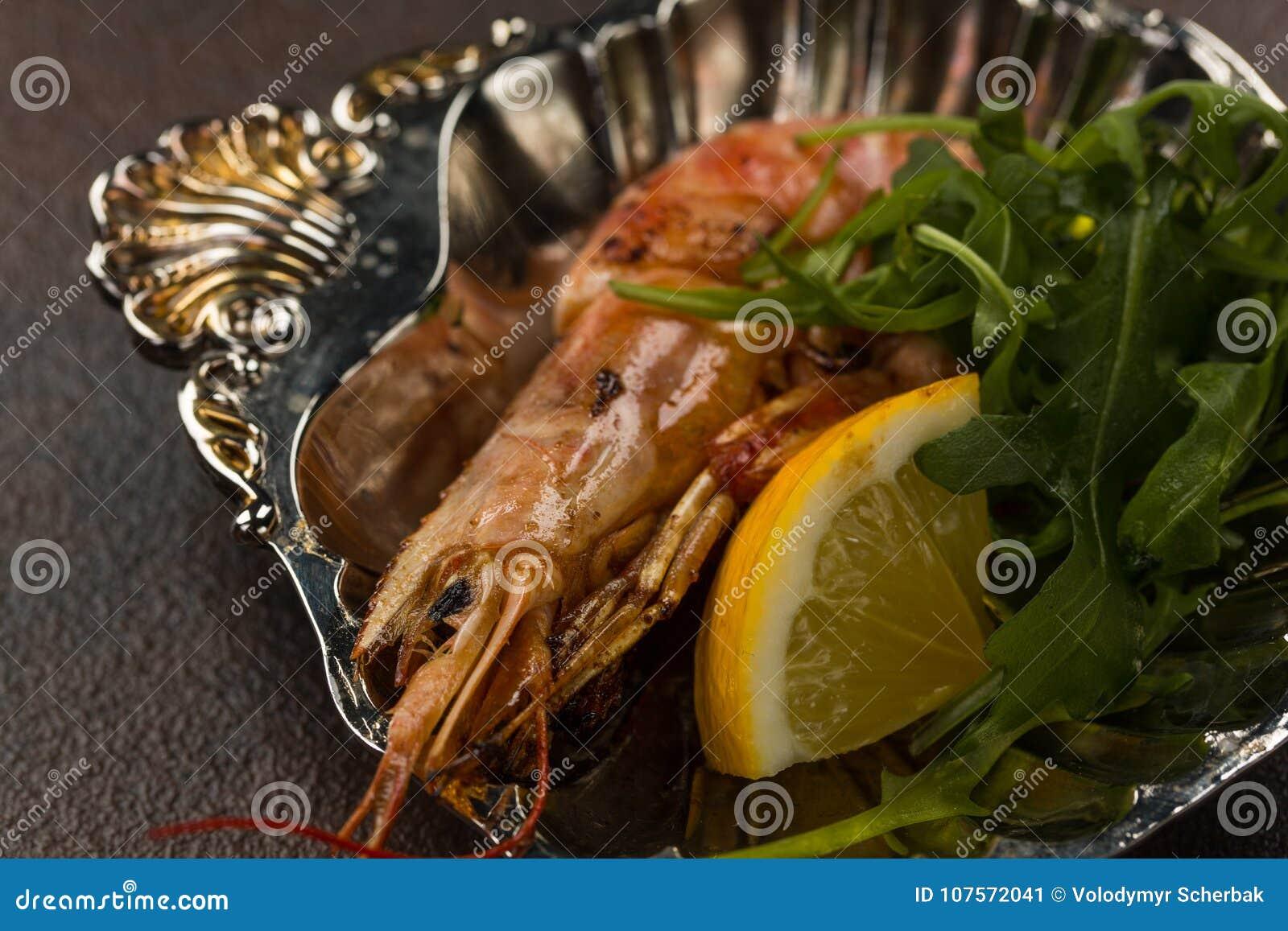 Man stekte på det stora tigerräkahuvudet med citronen och rukkola på den forntida plattan