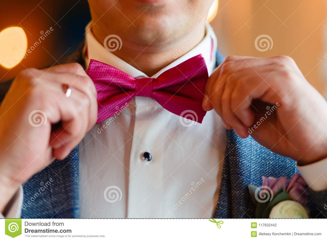A man in a stylish suit corrects a pink butterfly. Closeup of a corporate man adjusting his fashionable pink tie. Business concept