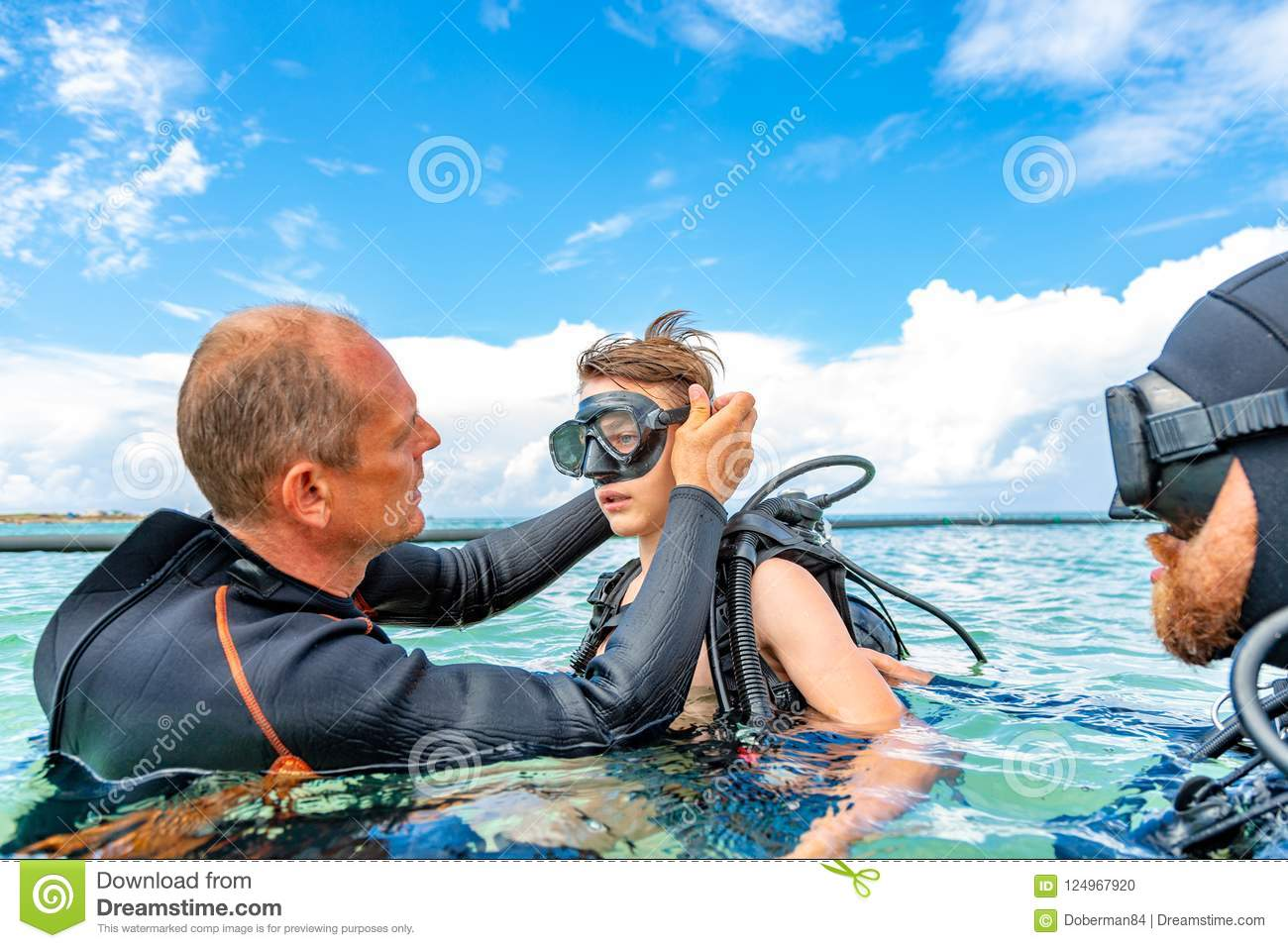 A man in a suit for diving prepares a boy to dive